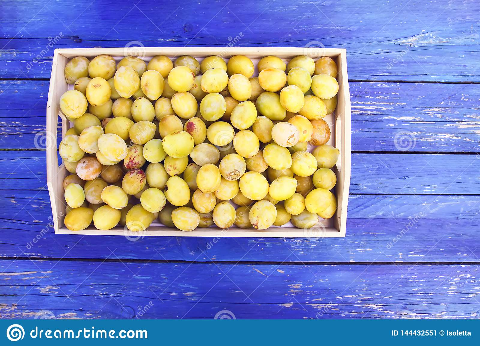 Fresh yellow plums. Ripe fruits in a wooden box on blue boards background.