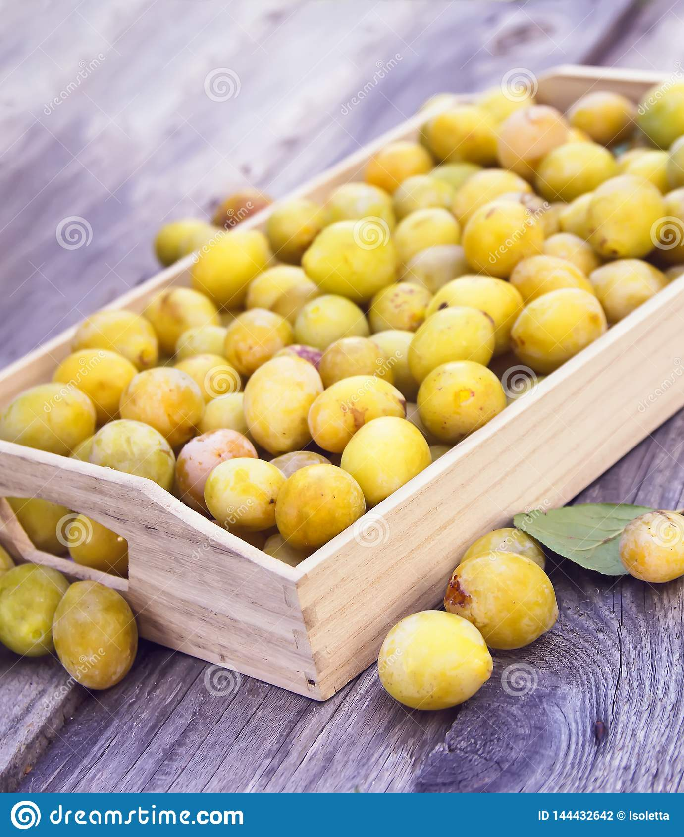 Fresh yellow plums. Ripe fruits in a wooden box on rough boards background