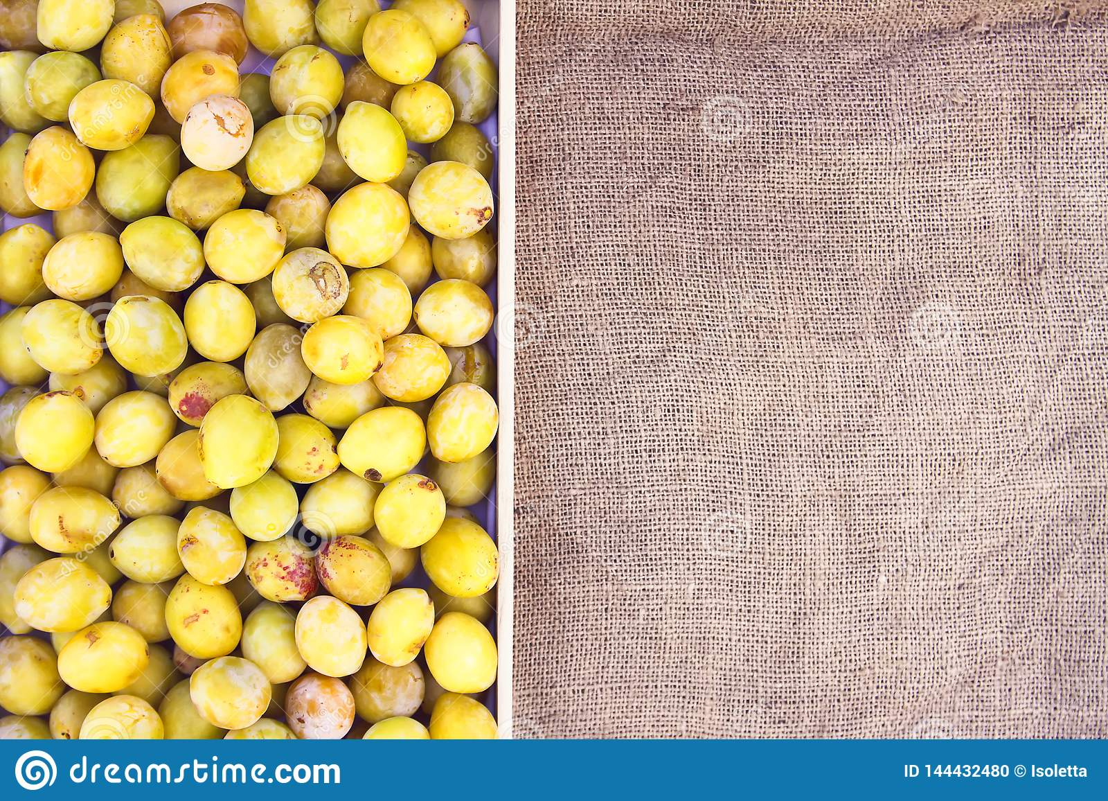 Fresh yellow plums. Ripe fruits in a wooden box on rough burlap