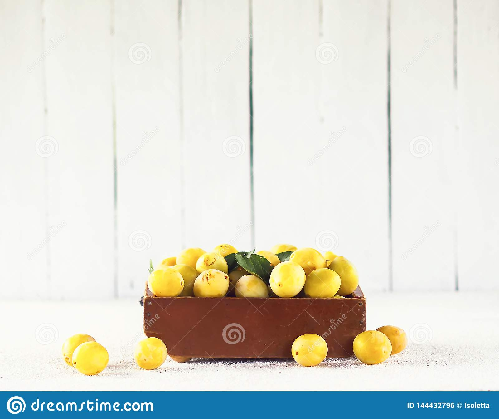 Fresh yellow plums. Ripe fruits in a wooden box on white boards