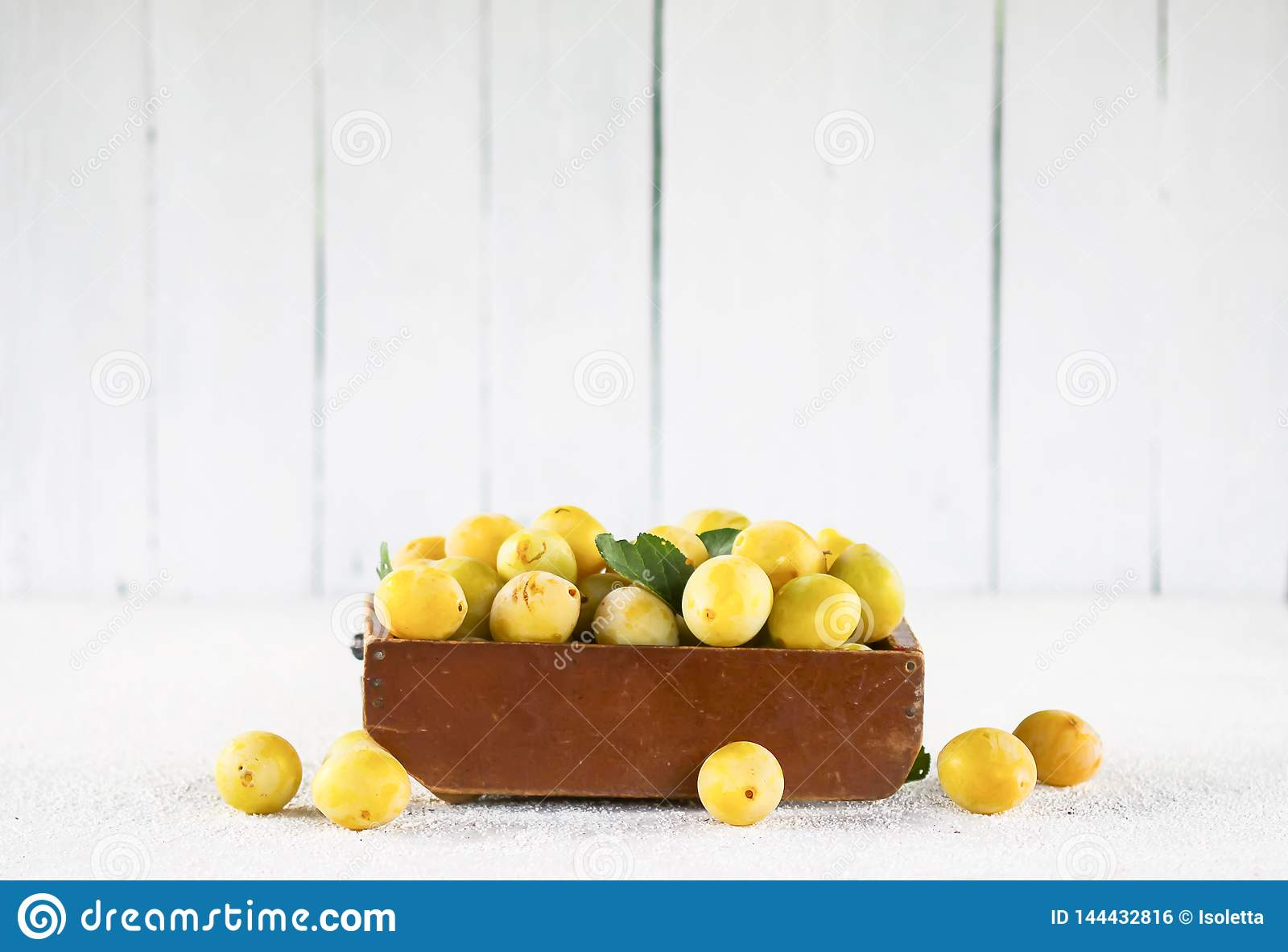 Fresh yellow plums. Ripe fruits in a wooden box on white boards background