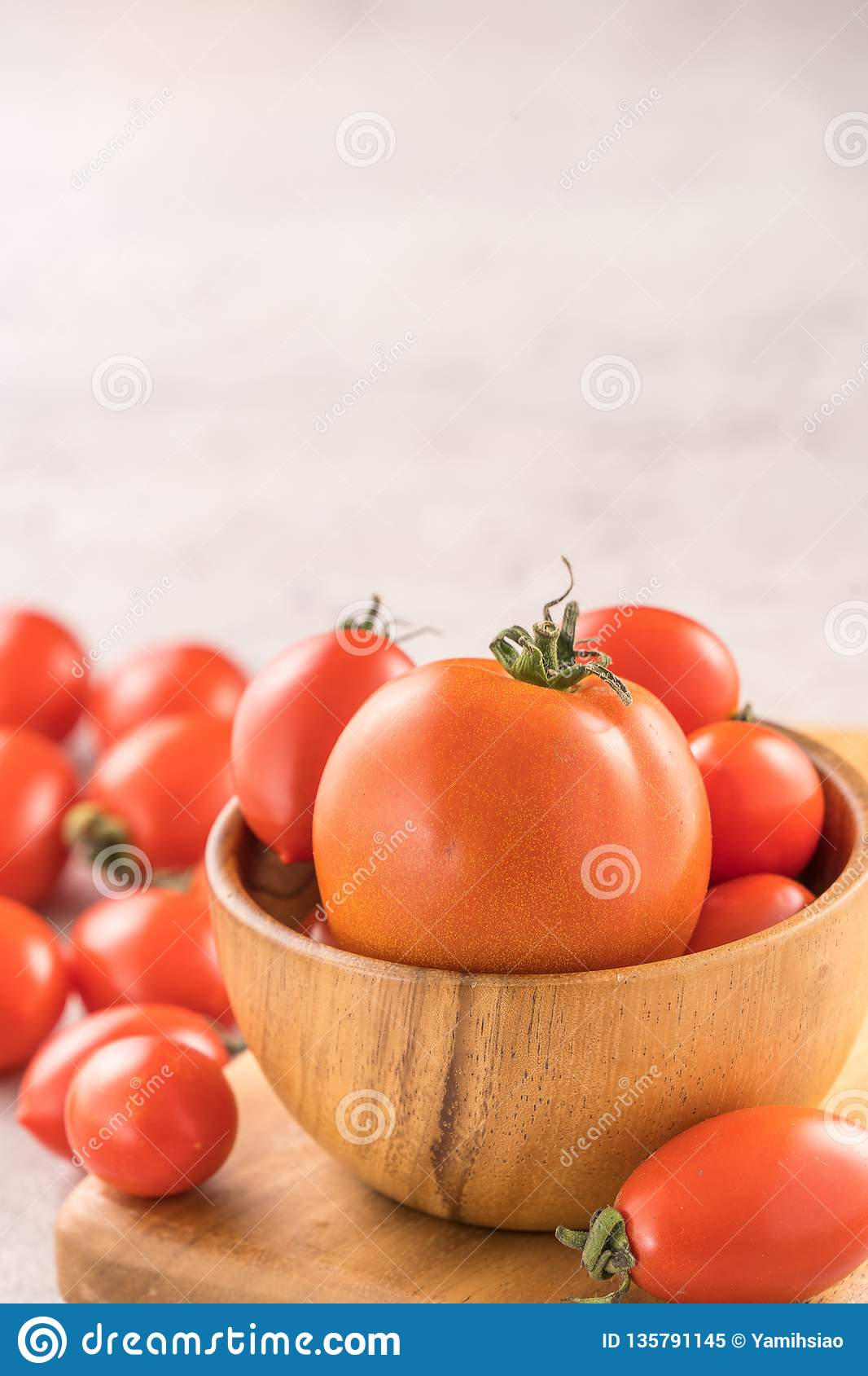 Fresh yellow and red cherry tomatoes in a basket on a cement board, close up, copy space, top view