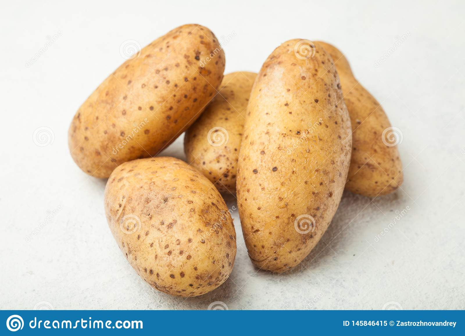 Fresh young potatoes on a white table