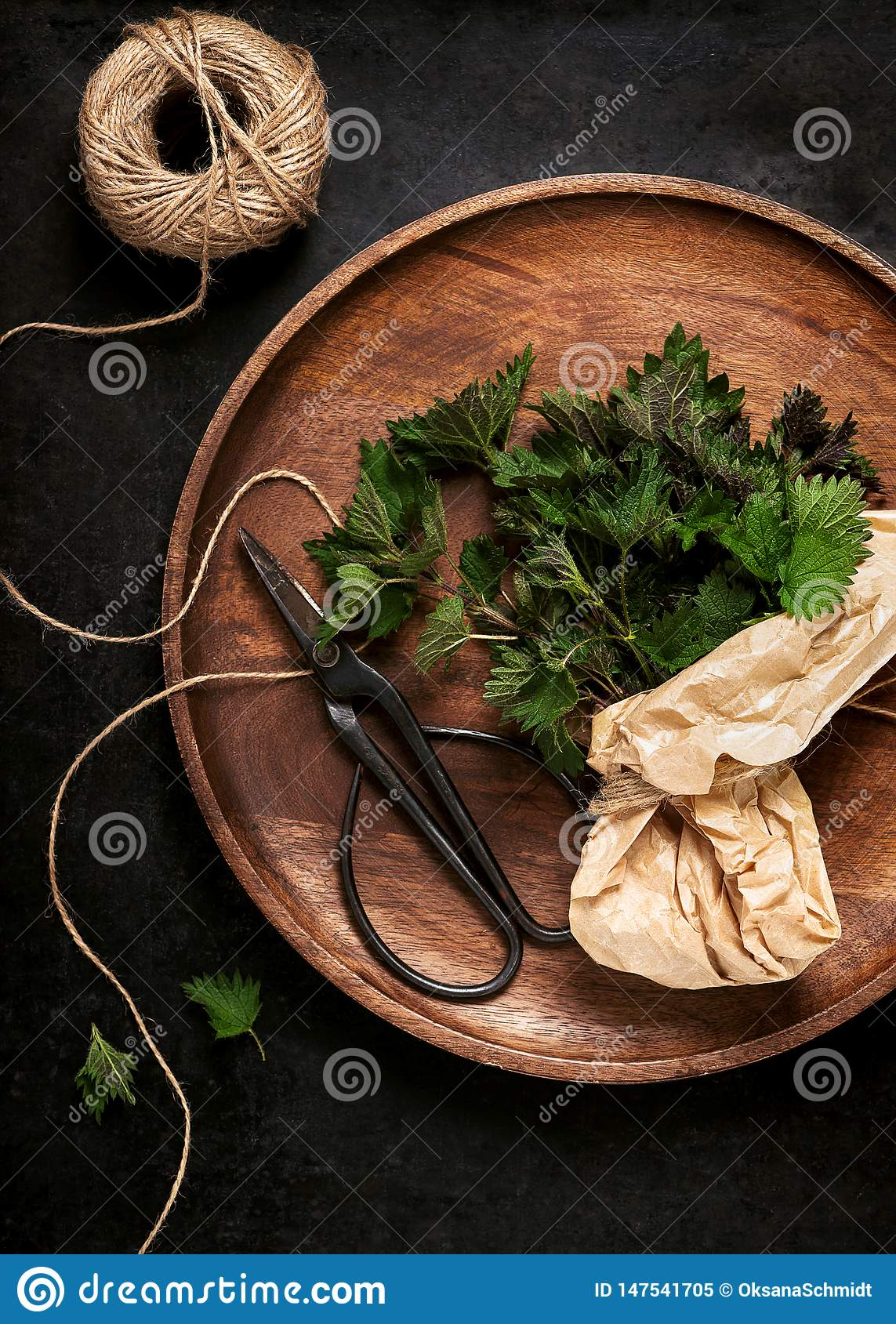 Fresh young stinging nettle leaves on a wooden pate.
