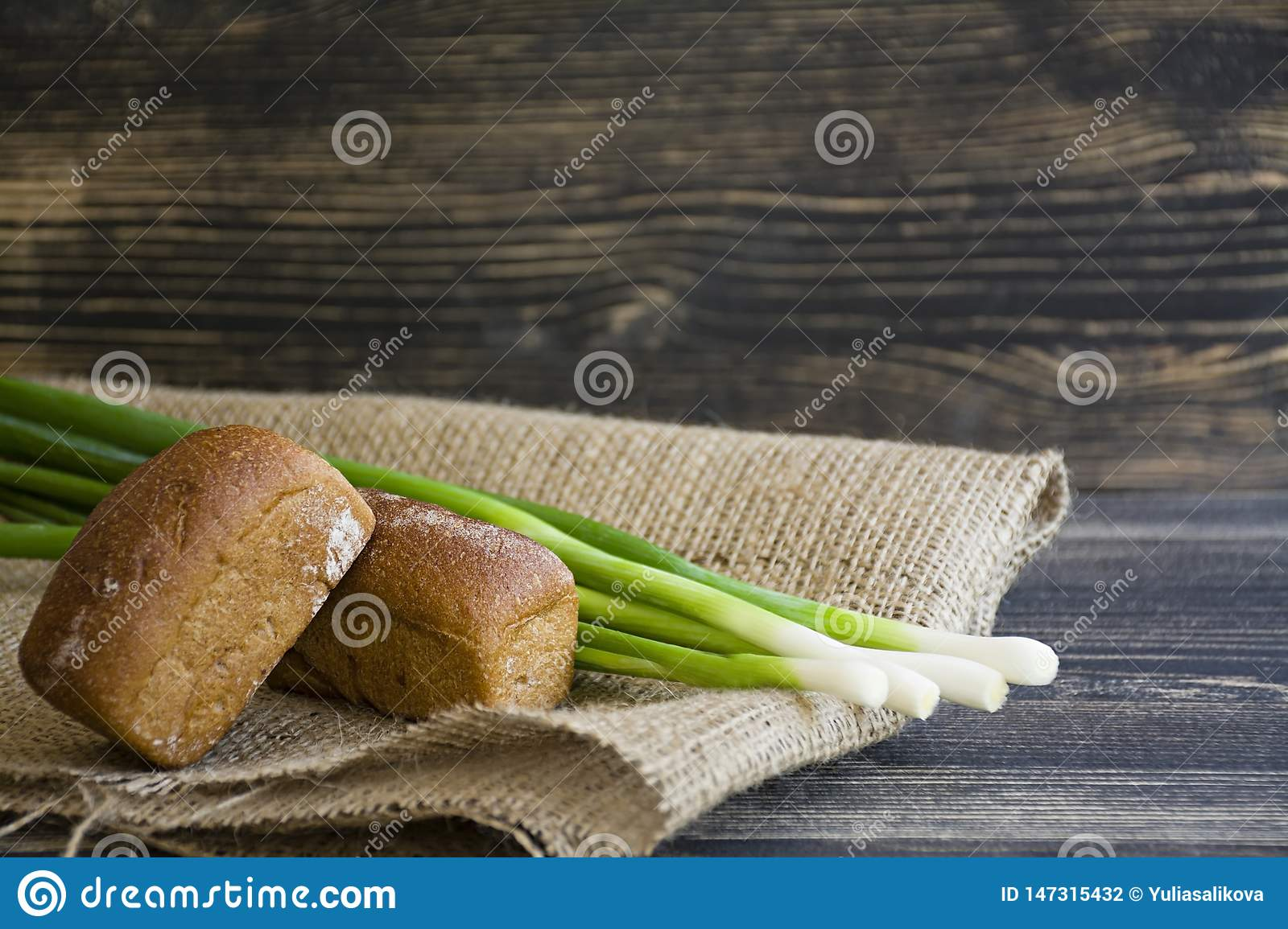Freshly baked bread and green onion on a dark wooden background