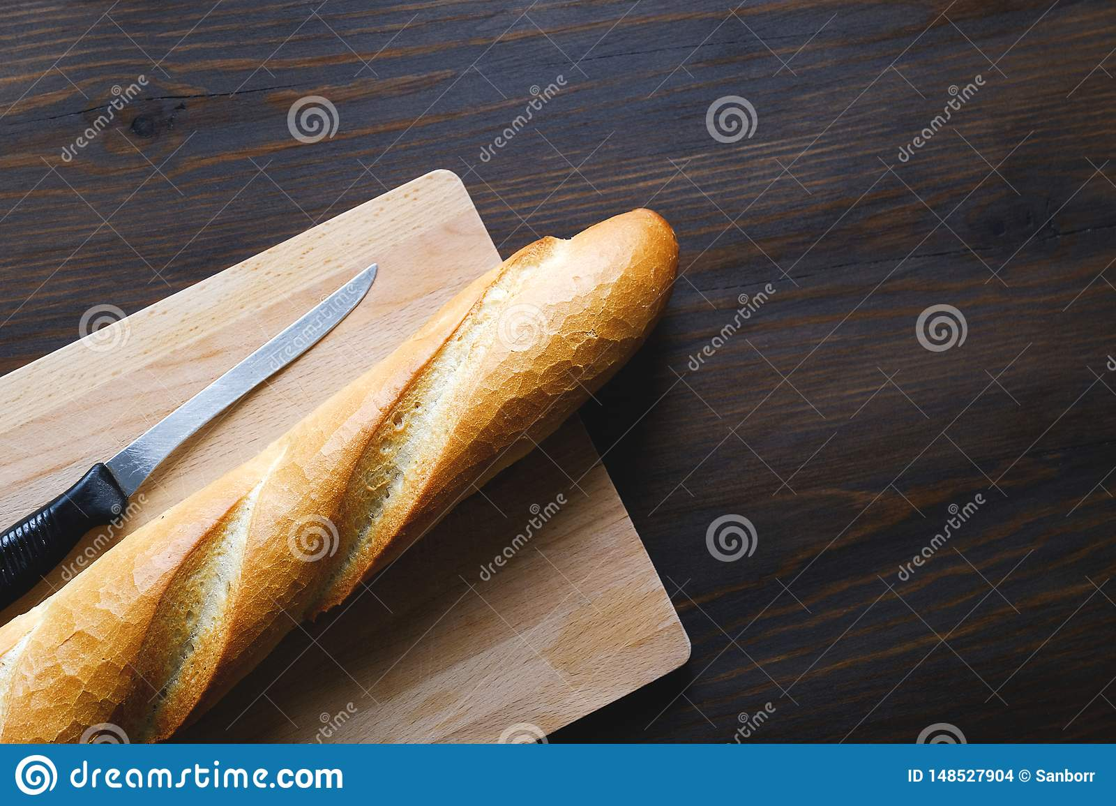 Freshly baked bread, kitchen knife with black plastic handle, cutting Board on a wooden table, close-up. Copy space for text. The