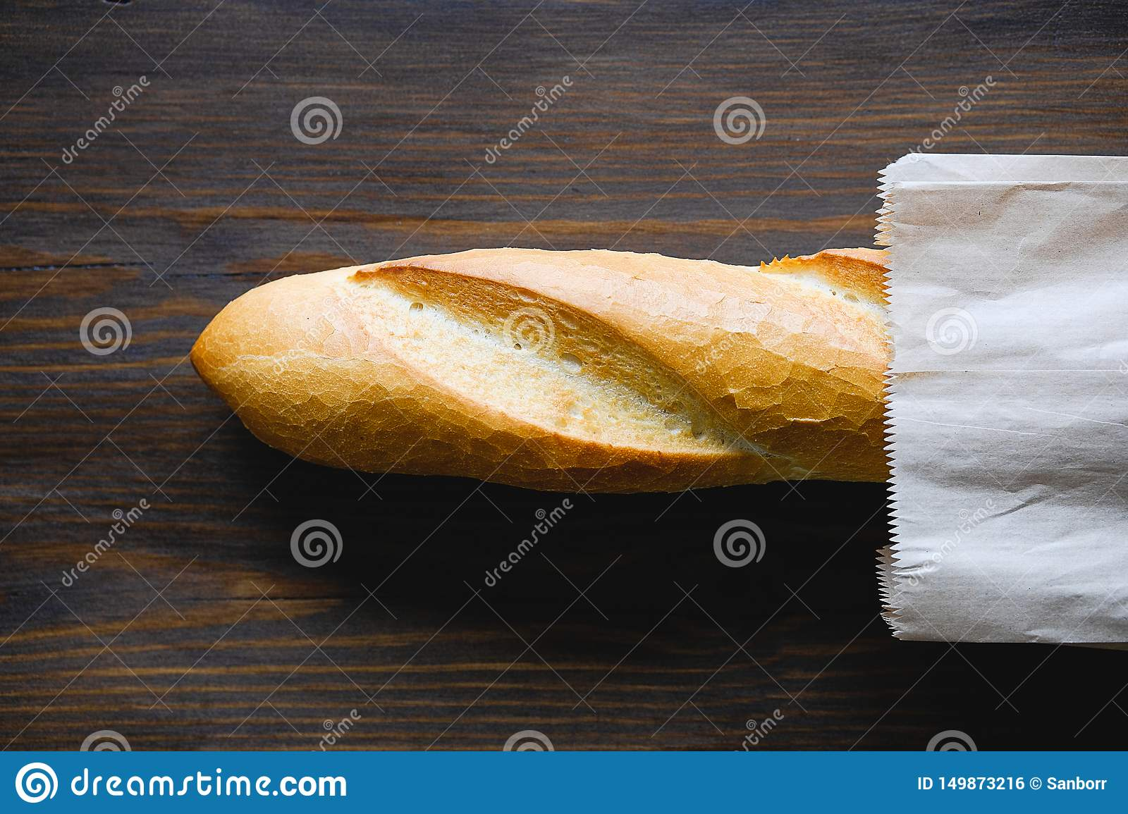 Freshly baked bread in a paper bag or package, on a cutting Board, on a brown wooden table, close-up. Copy space for text. The