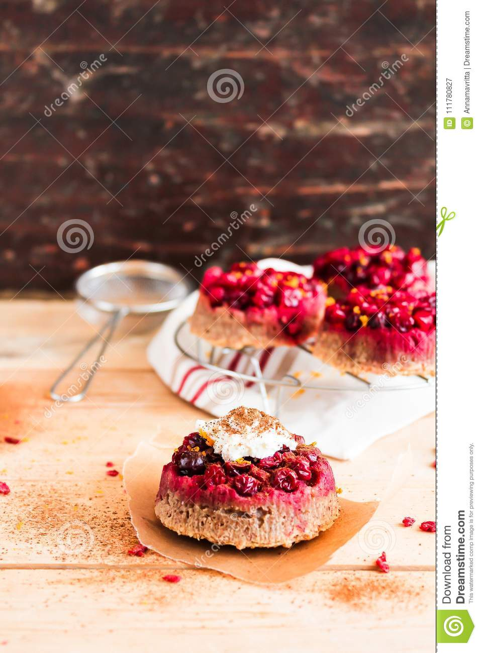 Freshly baked cranberry mini cakes on a wooden table, selective focus. Easter cakes.
