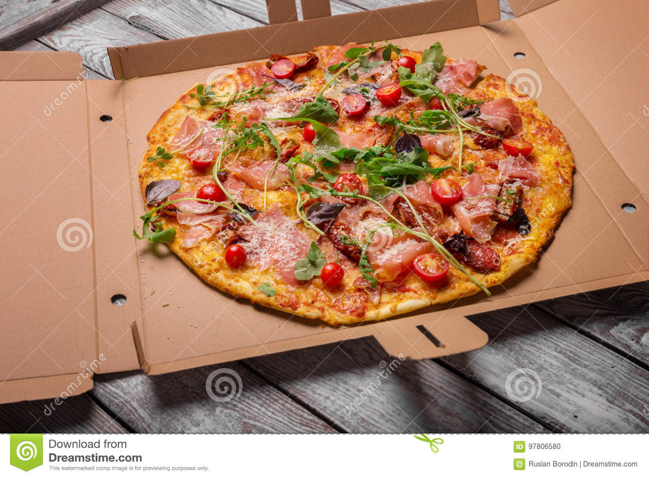Freshly baked pizza. Spicy, meaty, cheese pizza in a carton box. Pizza on a gray background. Pizzeria delivery concept.