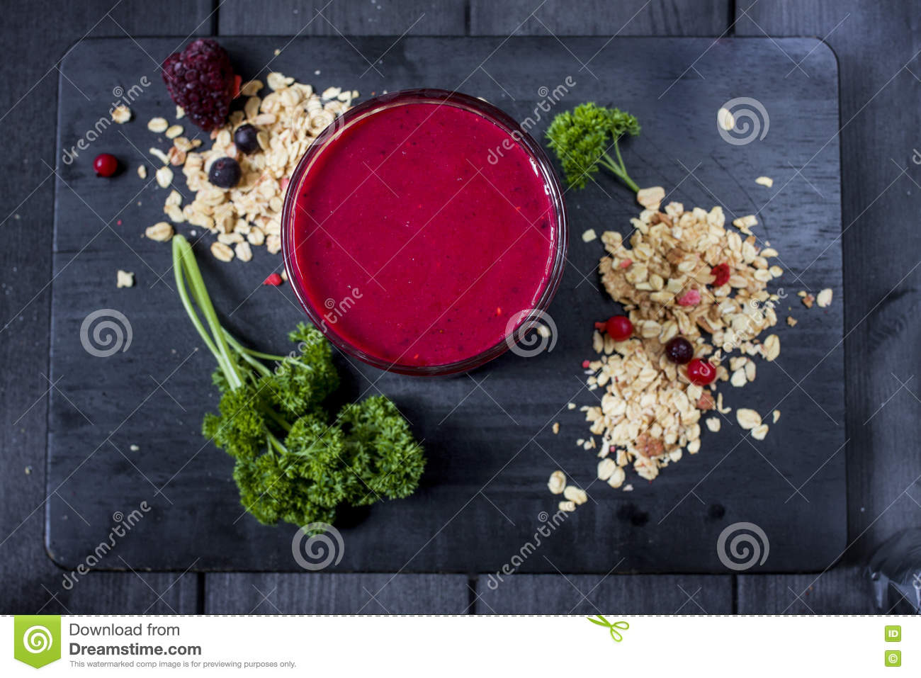 Freshly blended berry smoothie in a glass and granola on dark rustic wooden background. Selective focus, copy space