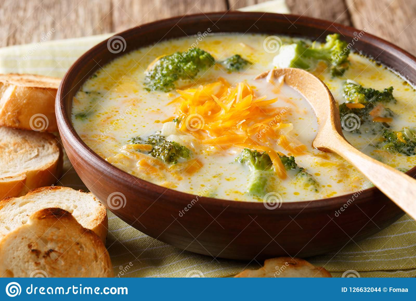 Freshly cooked broccoli cheese soup in a bowl with toast close-up. horizontal