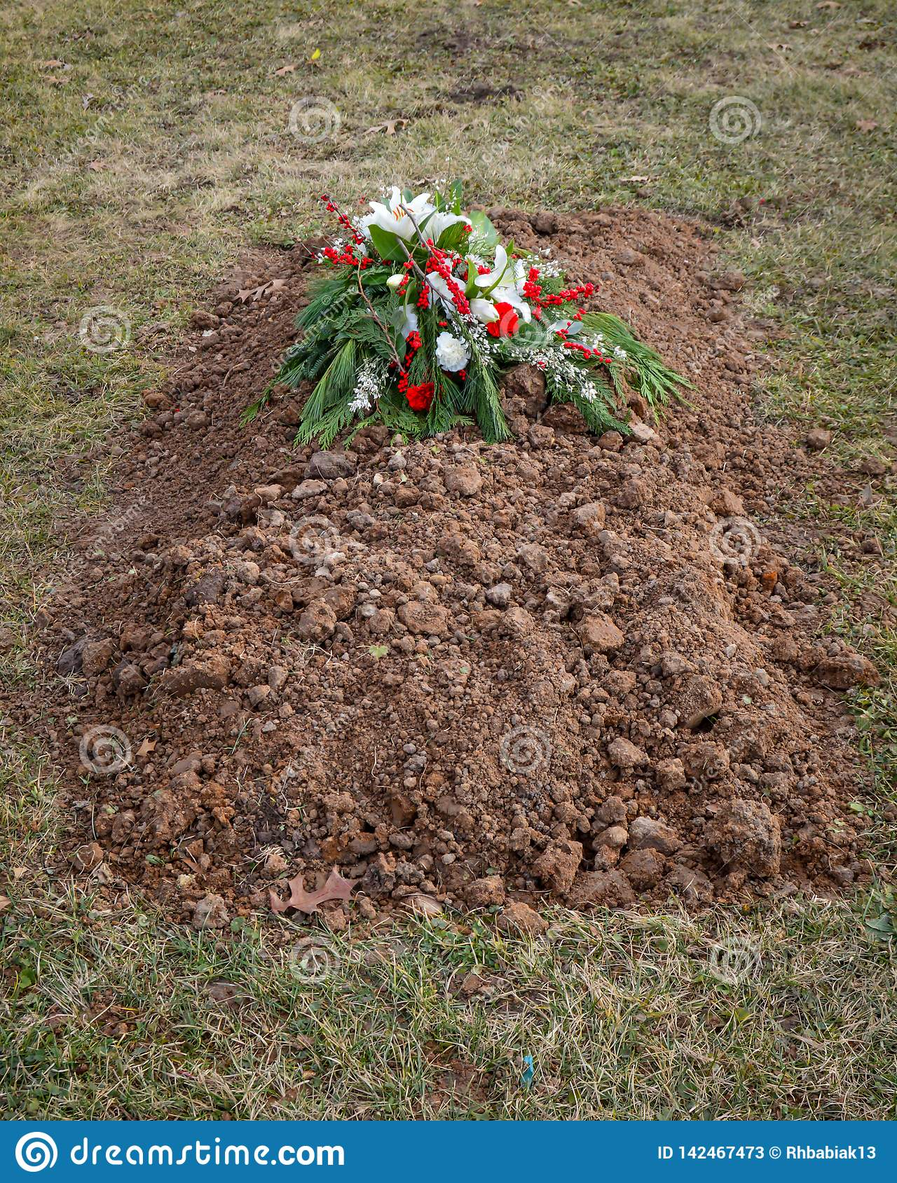 Freshly Dug Grave with Cemetery Flowers on Top of Ground