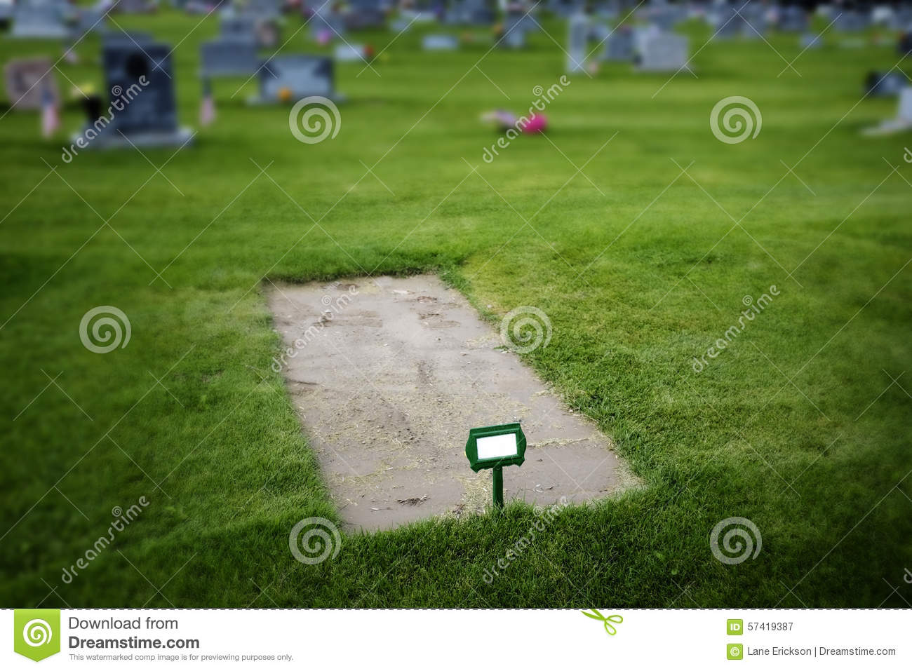 Freshly Dug Grave in Cemetery with Headstones and Green Grass