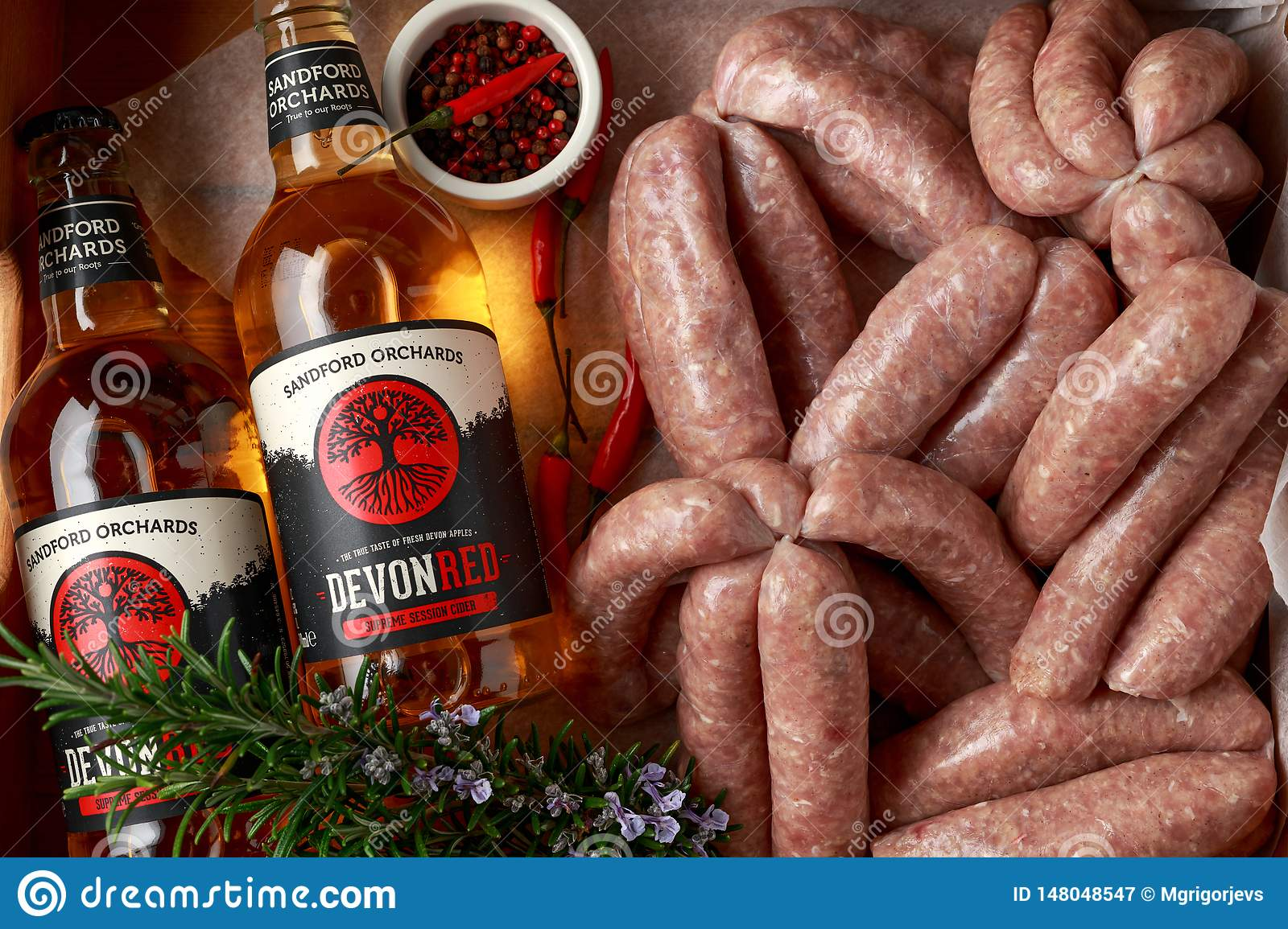 Freshly made raw butchers sausages in skins with Sanford orchards apple cider, Devon, United Kingdom, March 20, 2019.