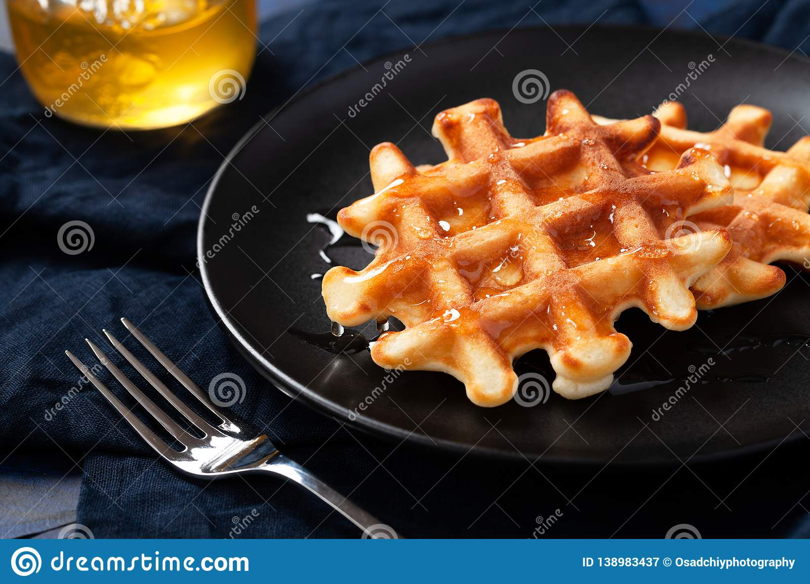 Freshly prepared belgian waffles with honey or maple syrup