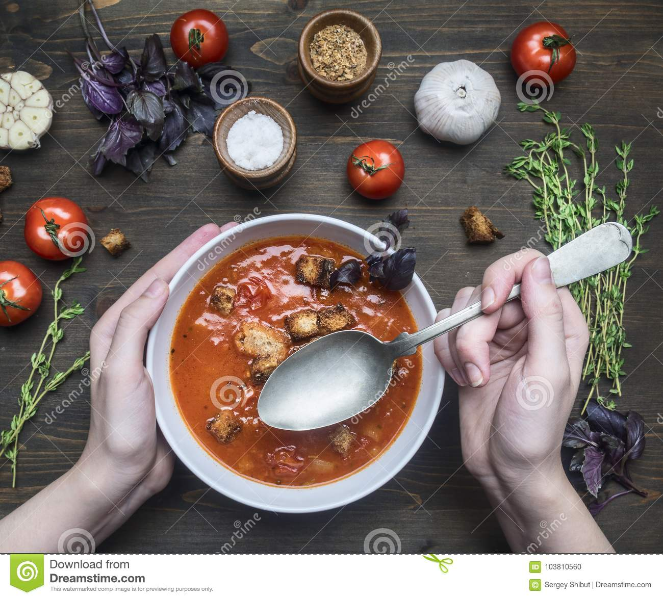 Freshly prepared tomato soup with basil, garlic and onion, thyme and seasonings, in a white plate, girl scooped up a spoon, on