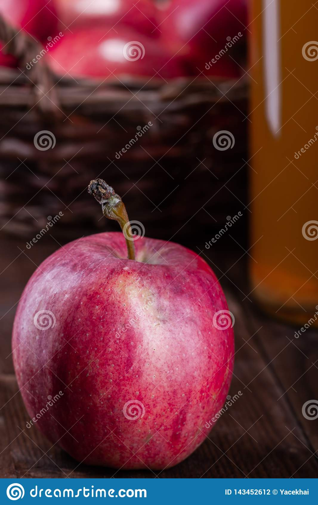 Red, organic apple. Fruit in a wooden basket on a wooden table.
