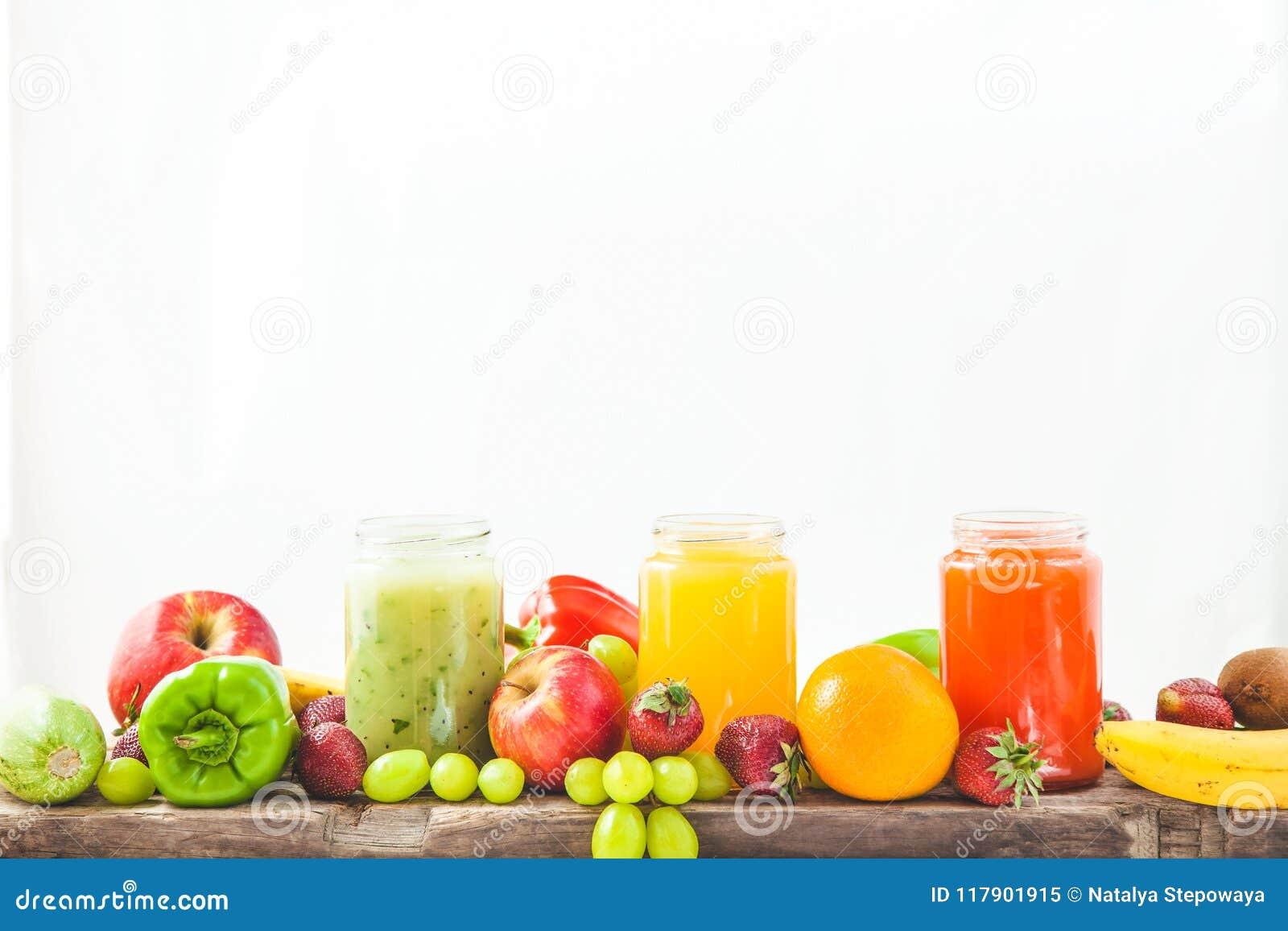 Freshly squeezed fruit juice, smoothies yellow orange green blue banana lemon apple orange kiwi grape strawberry on a white isolat