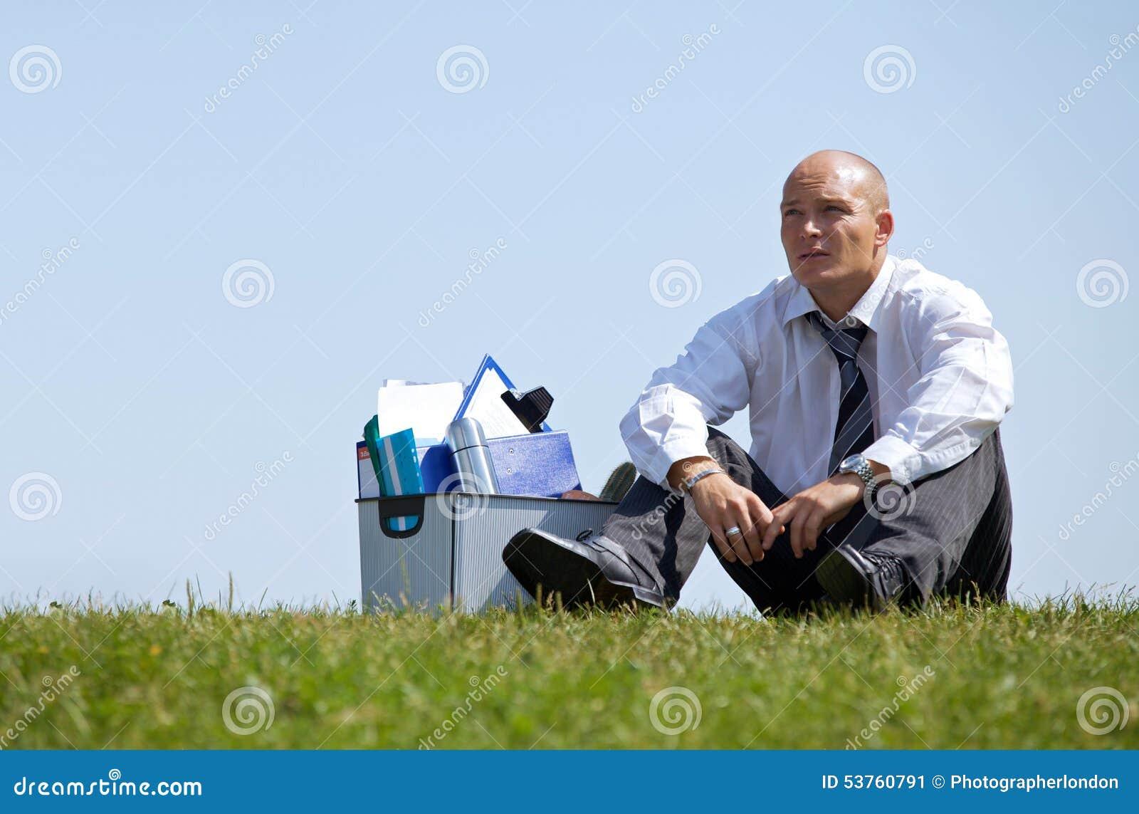 Freudloser Geschäftsmann, der voll nahe bei Korb von Dateien im Park sitzt