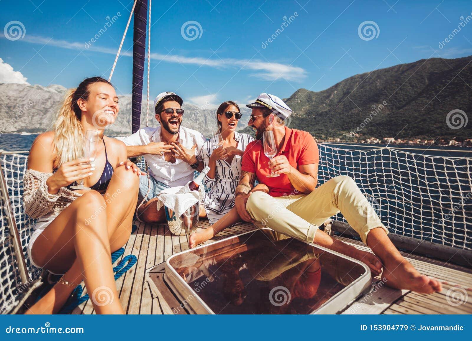Freunde, die auf Segelbootplattform sitzen und Spaß haben Ferien, Reise, Meer, Freundschaft und Leutekonzept