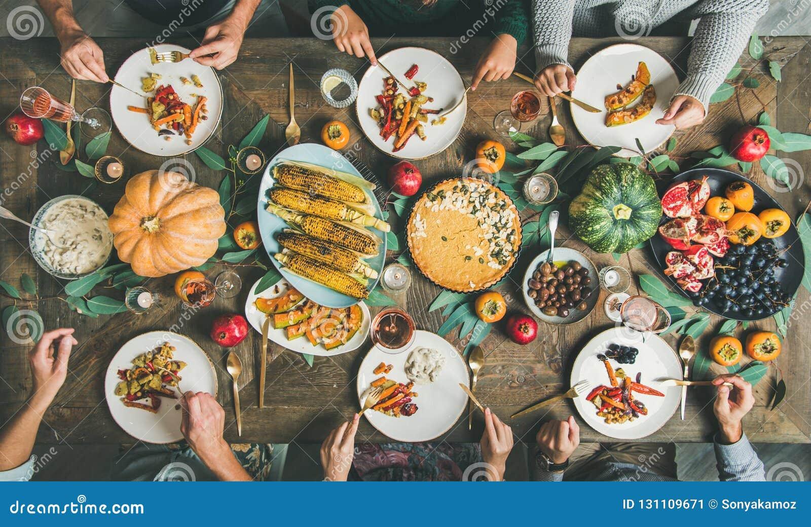 Freunde, die am Danksagungs-Tagestisch mit vegetarischen Imbissen essen