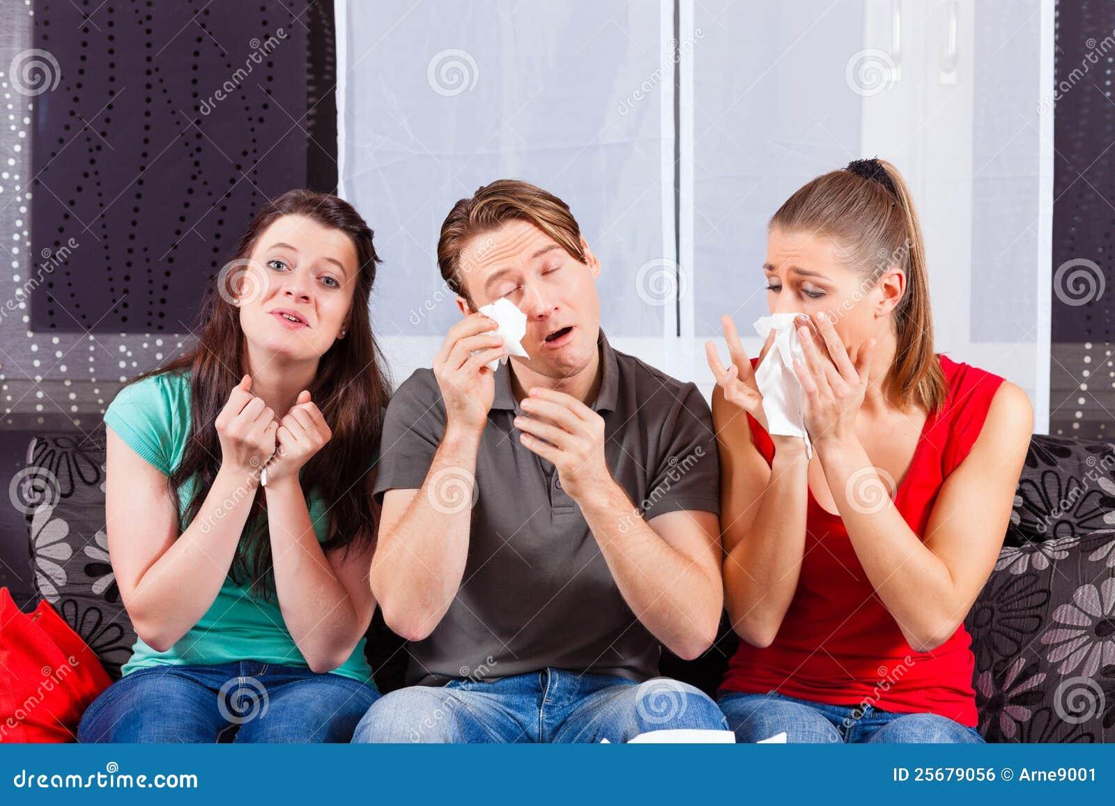 Freunde, die einen traurigen Film in Fernsehapparat überwachen