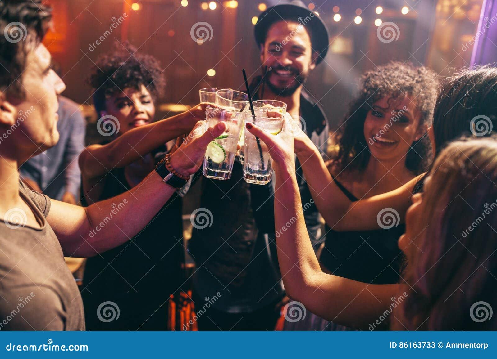 Freunde, die Getränke an der Nachtclubpartei haben