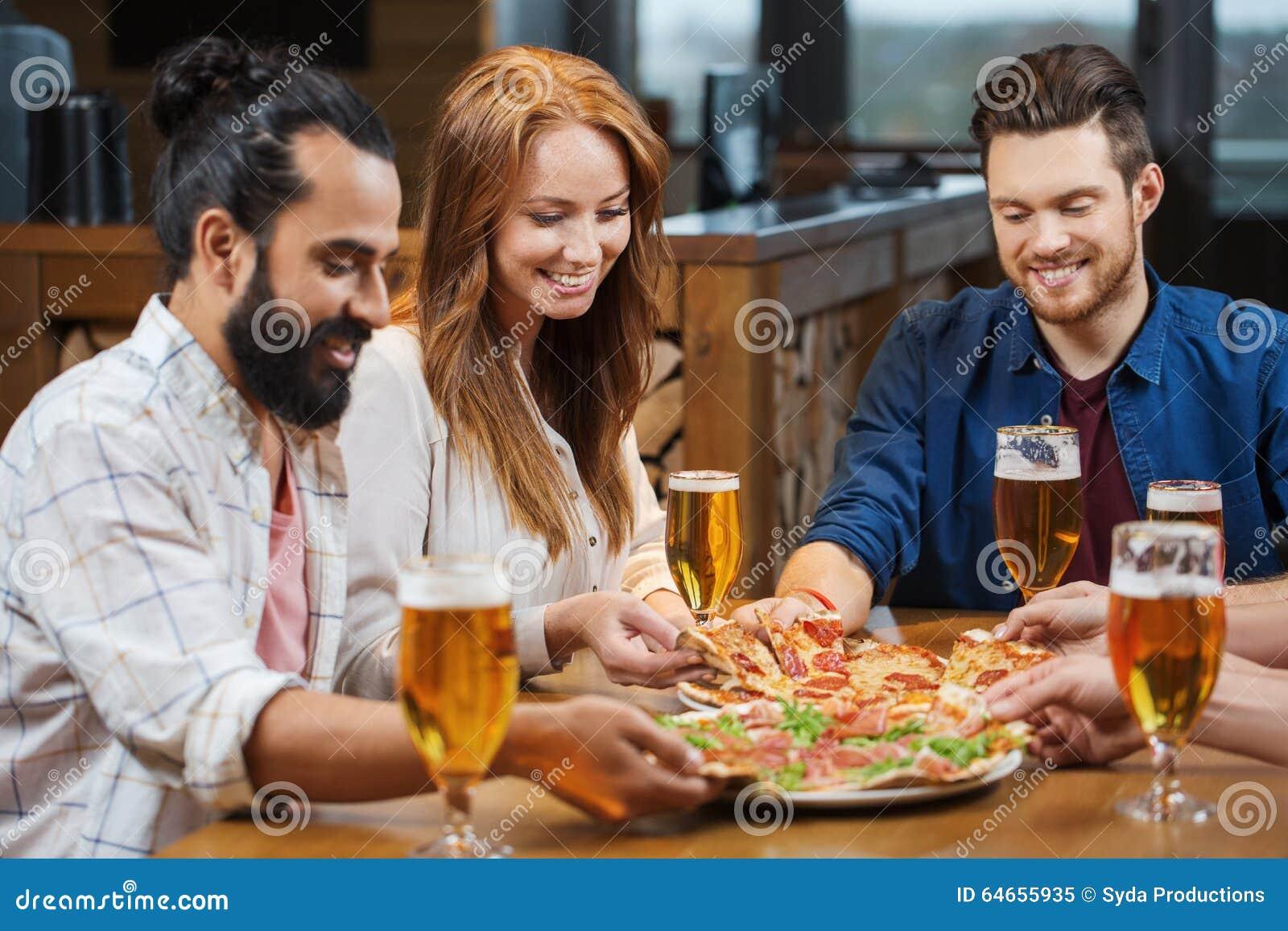 Freunde, die Pizza mit Bier am Restaurant essen