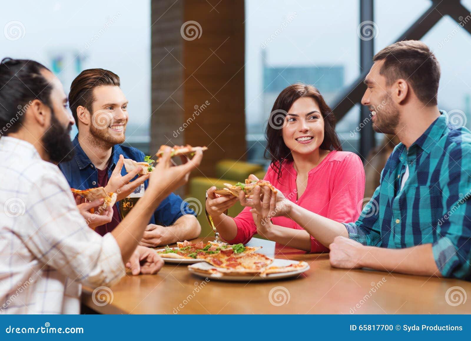 Glückliche Freunde essen im Restaurant — Stockfoto © Syda