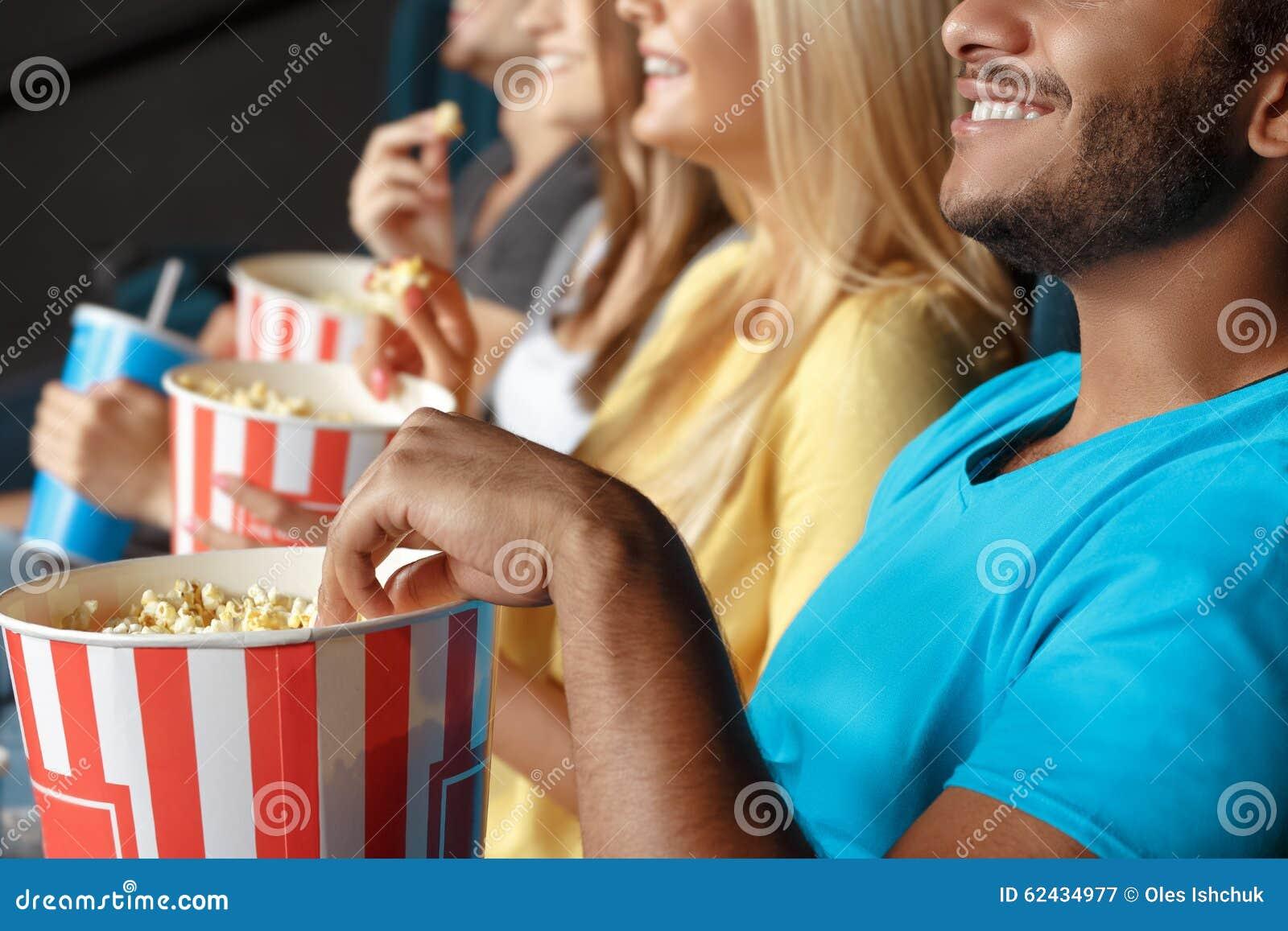 Freunde, die Popcorn am Kino essen
