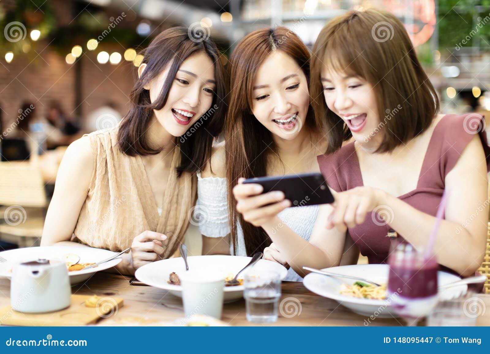 Freunde, die Telefon des Abendessens und des Aufpassens intelligentes im Restaurant haben