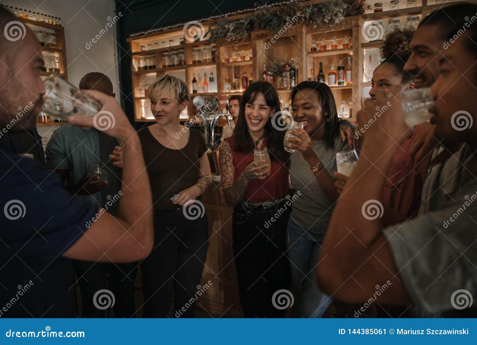 Freunde, die zusammen in einer Bar nachts trinken und sprechen