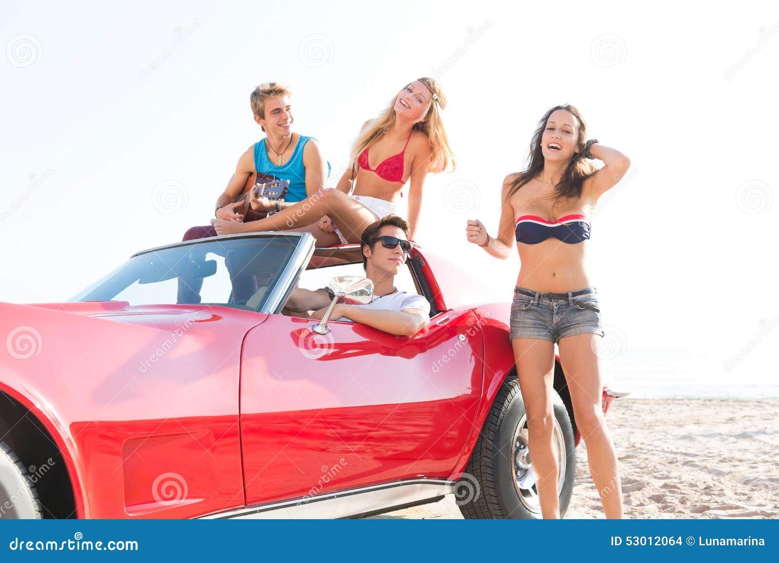 Freunde gruppieren am Strand im Sportautokabriolett
