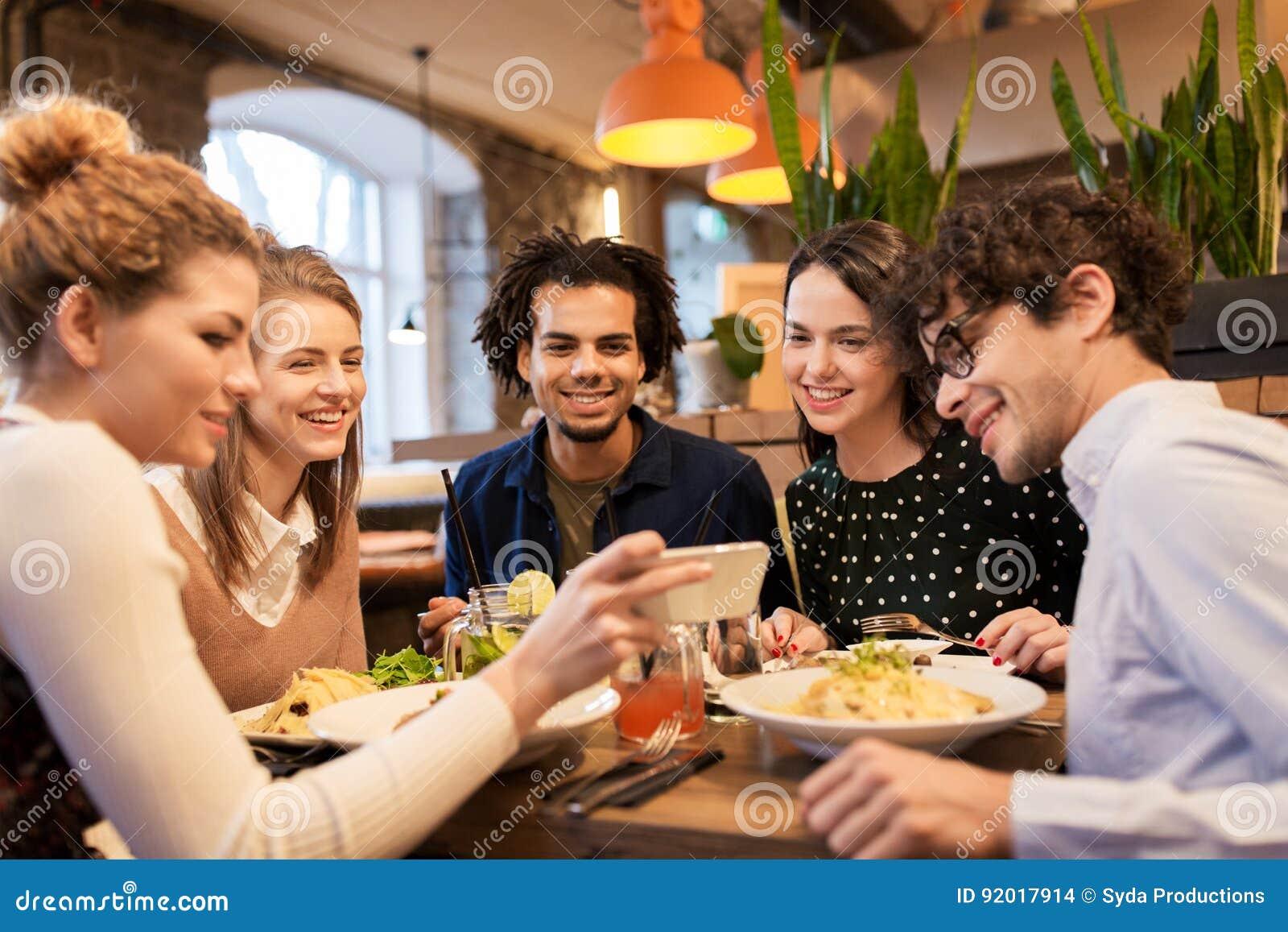 Freunde Mit Smartphones Essend Am Restaurant Stockbild