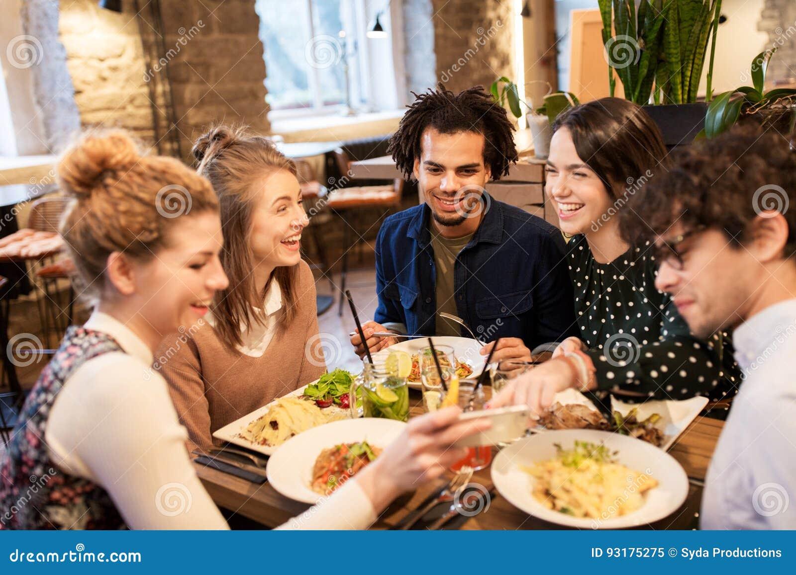 Freunde mit Smartphone essen im Restaurant — Stockfoto