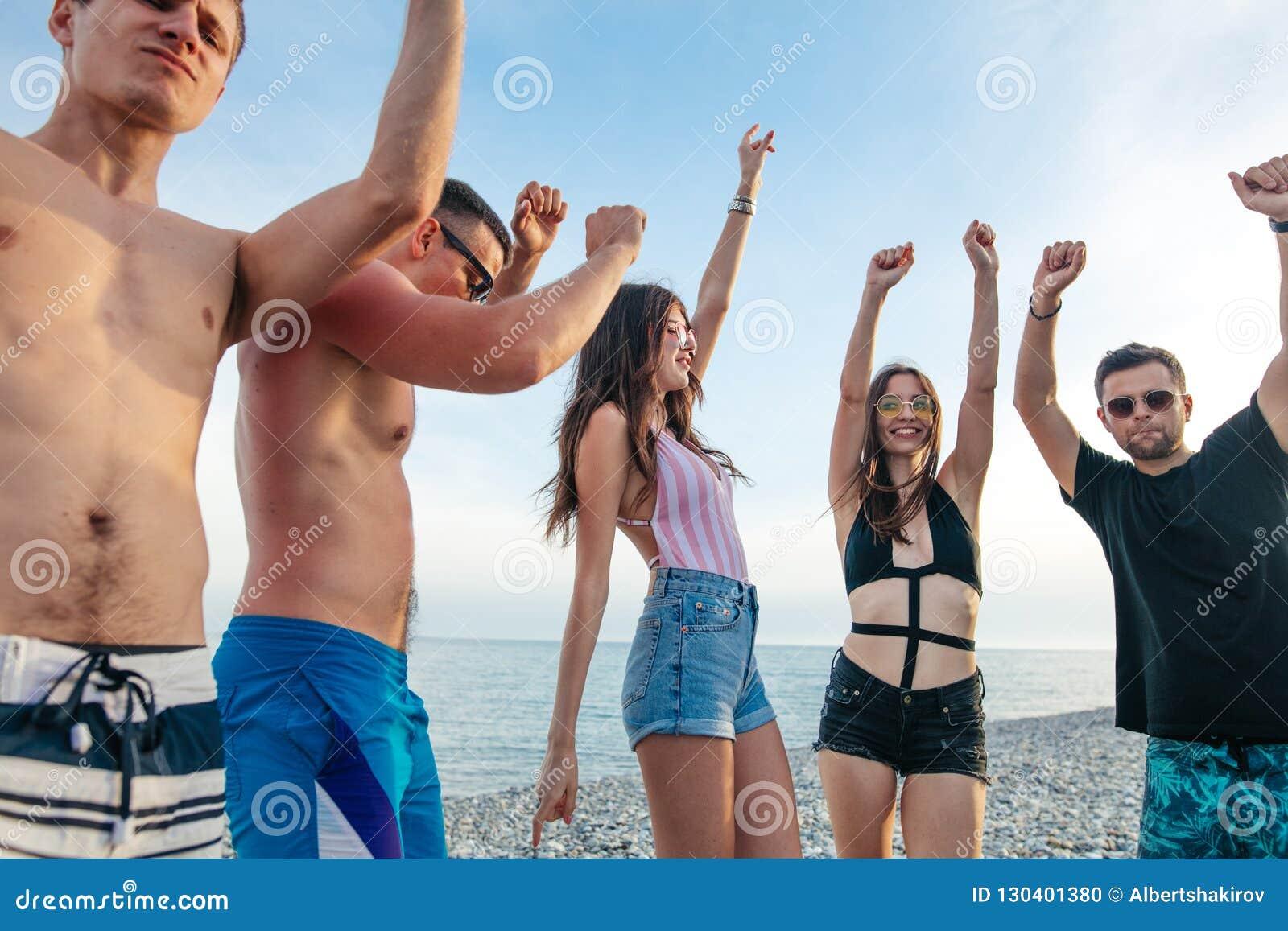 Freunde tanzen auf Strand unter Sonnenuntergangsonnenlicht und haben den Spaß, glücklich, genießen