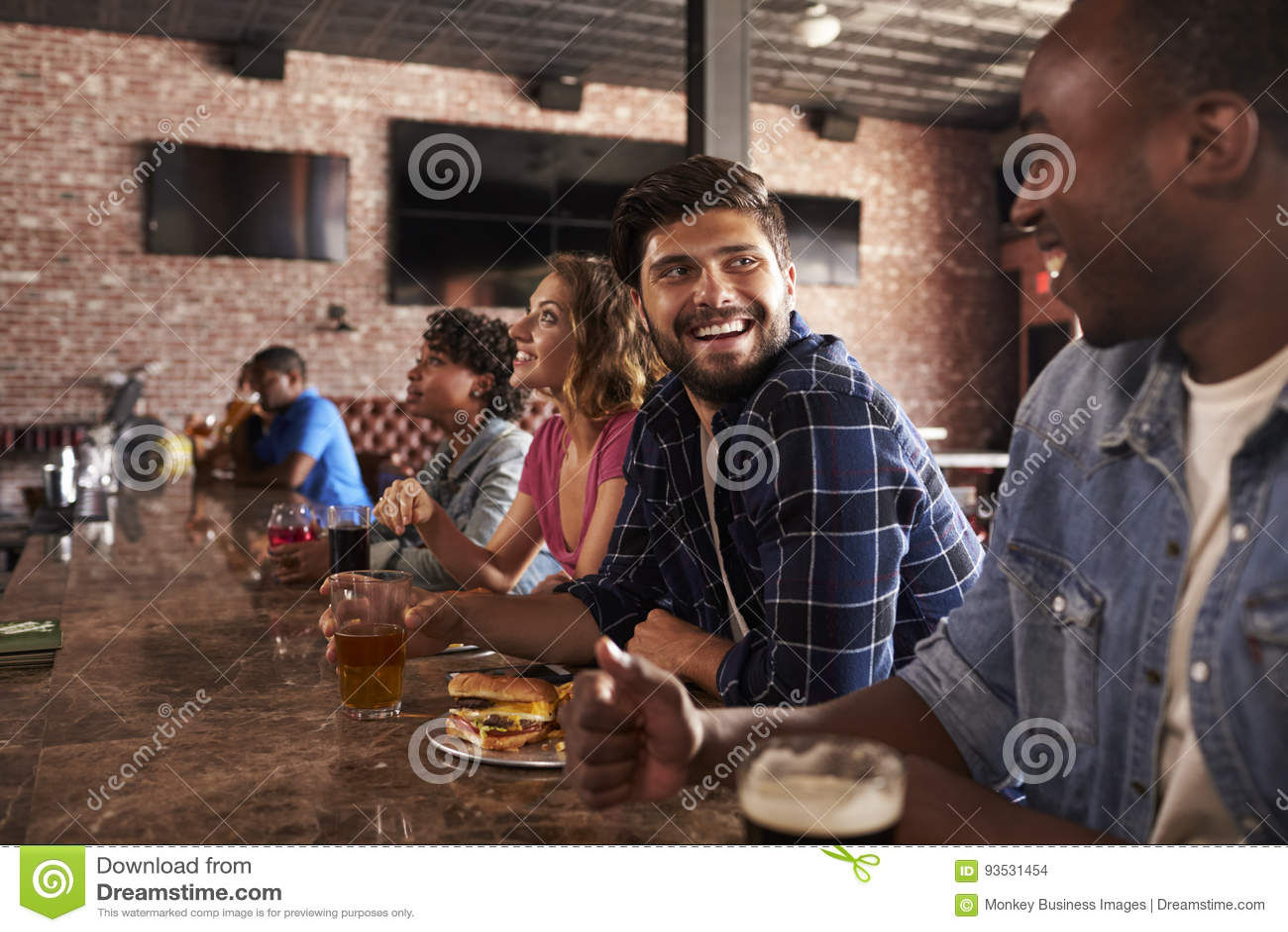 Freunde am Zähler in Sportbar-aufpassendem Spiel