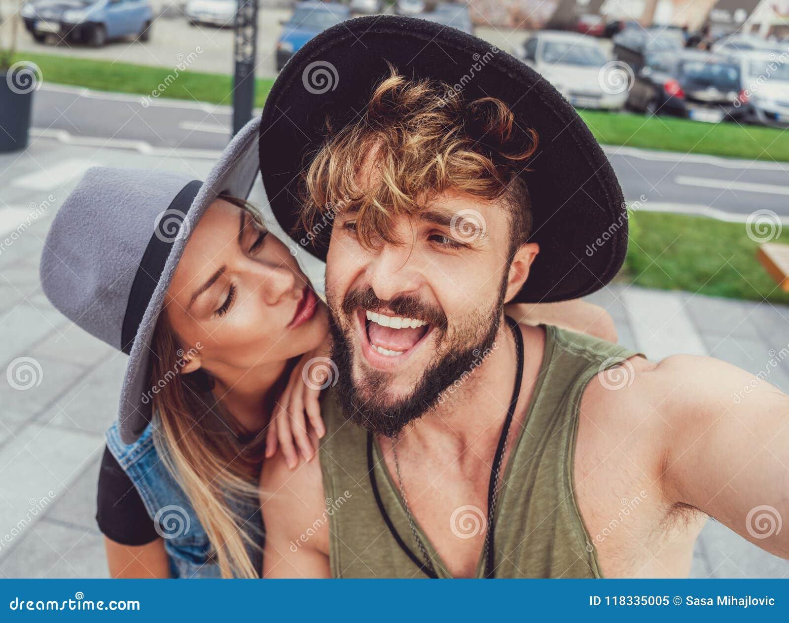 Freundin, die Freund küsst, während er selfie nimmt