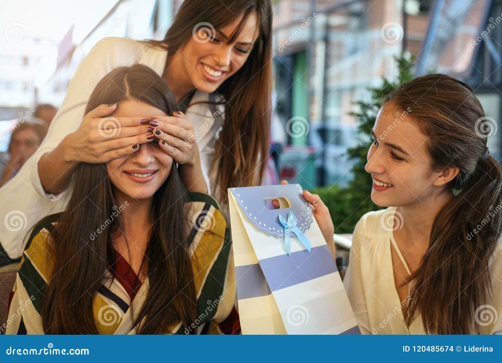 Freundinnen, die Geburtstagsgeschenk geben Mädchen überraschte ihren Freund