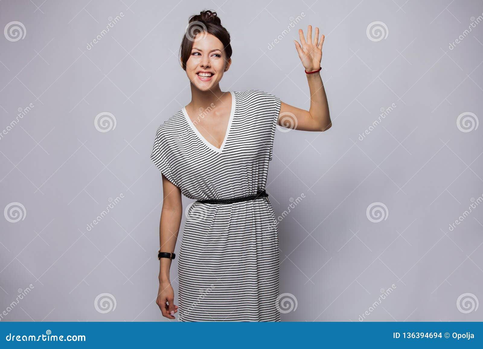 Freundliche Frau sagt hallo zu den neuen Nachbarn Porträt der reizend jungen emotionalen Frau, die mit der angehobenen Hand, Gruß