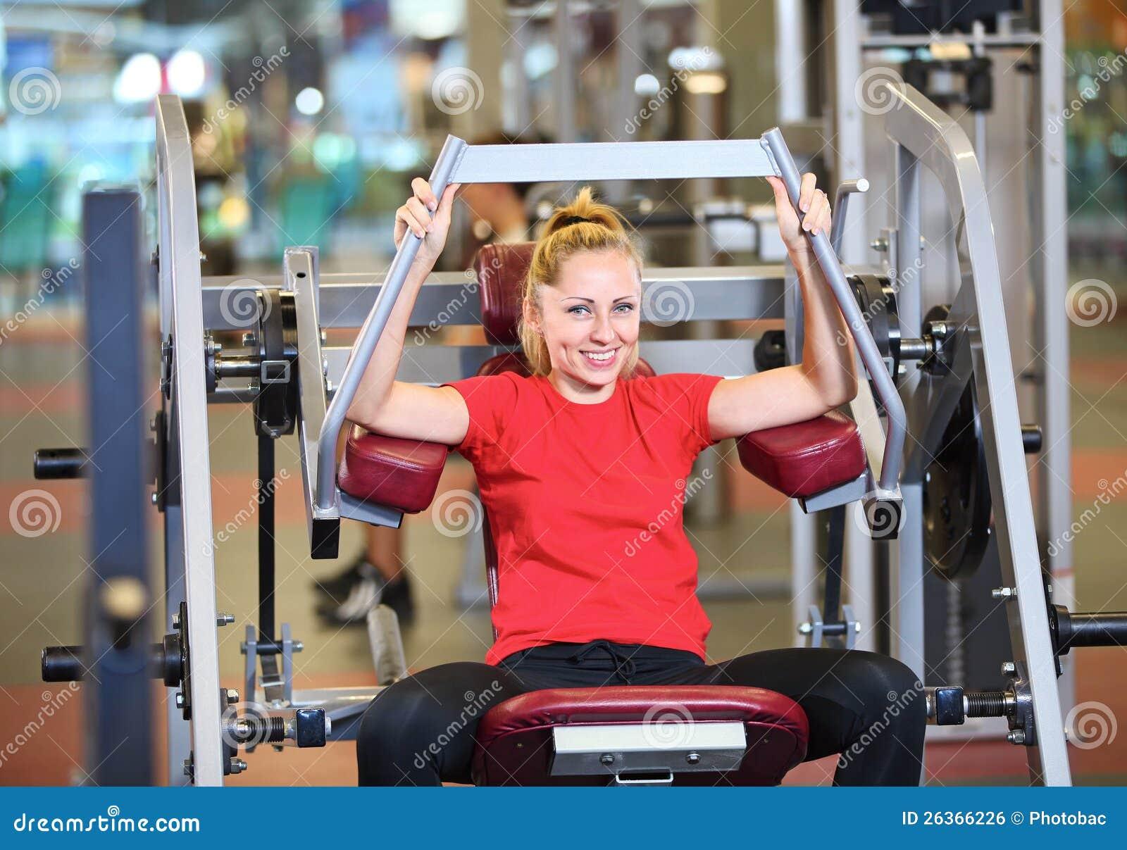 Freundliche junge Frau, die in der Gymnastik ausarbeitet