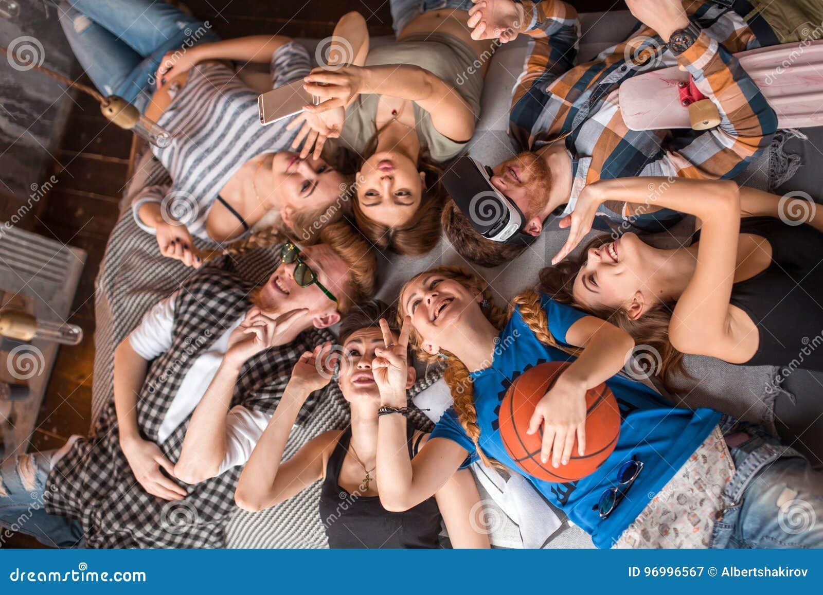 Freundschaft, Freizeit, Sommer und Leutekonzept - Gruppe lächelnde Freunde, die zuhause auf Boden im Kreis liegen