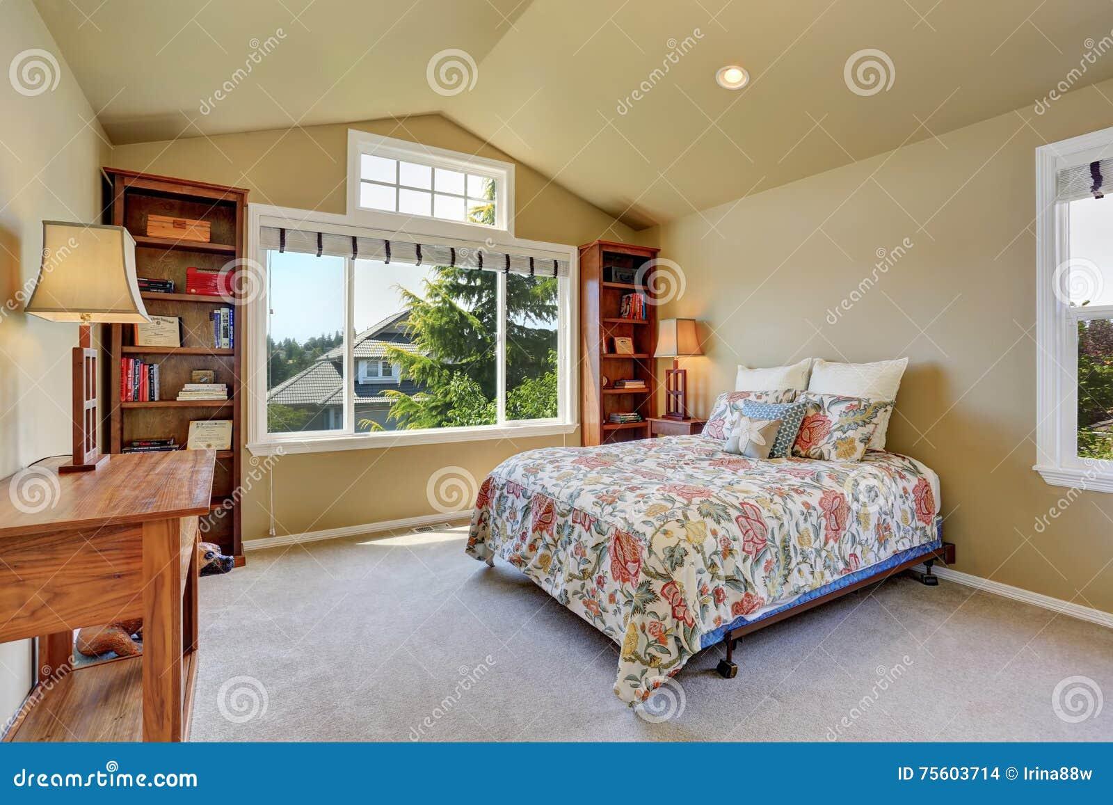 Färgrik säng och två bokfall i uppför trappan sovrum arkivfoto ...