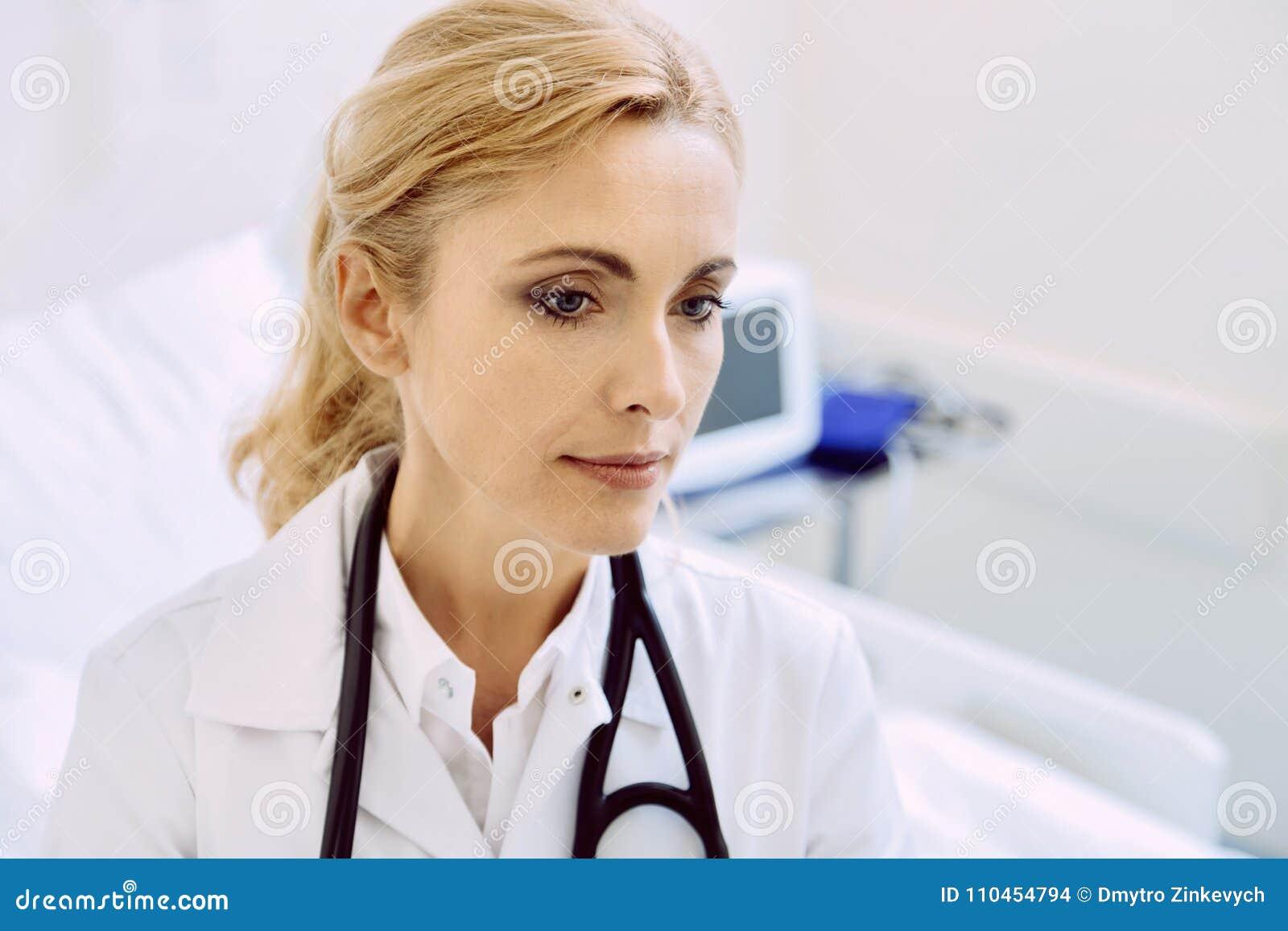 Fridfull kvinnlig doktor med stetoskopet på sjukhuset