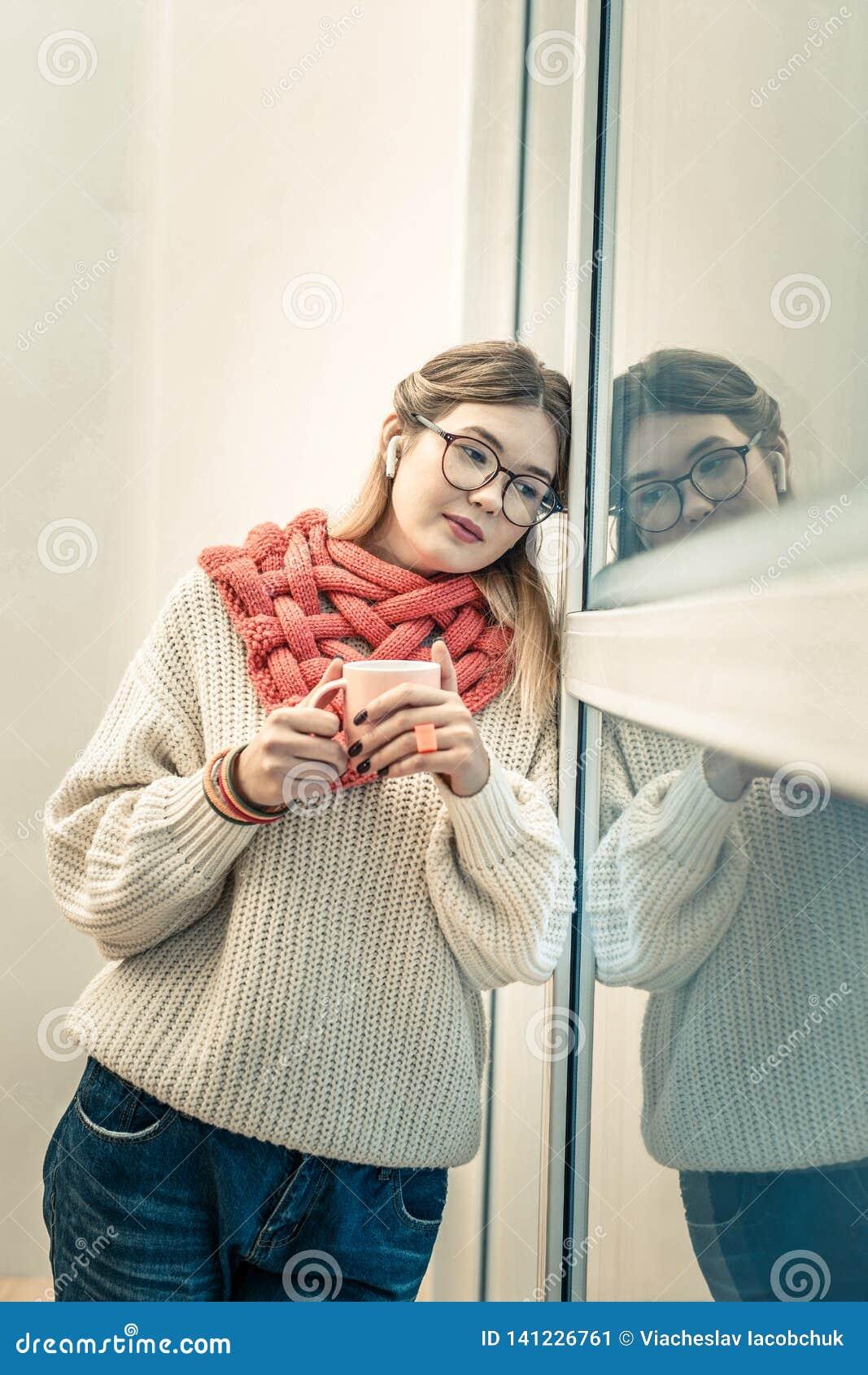 Fridsam lockande kvinna i den stack tröjan som lutar på plast- fönster