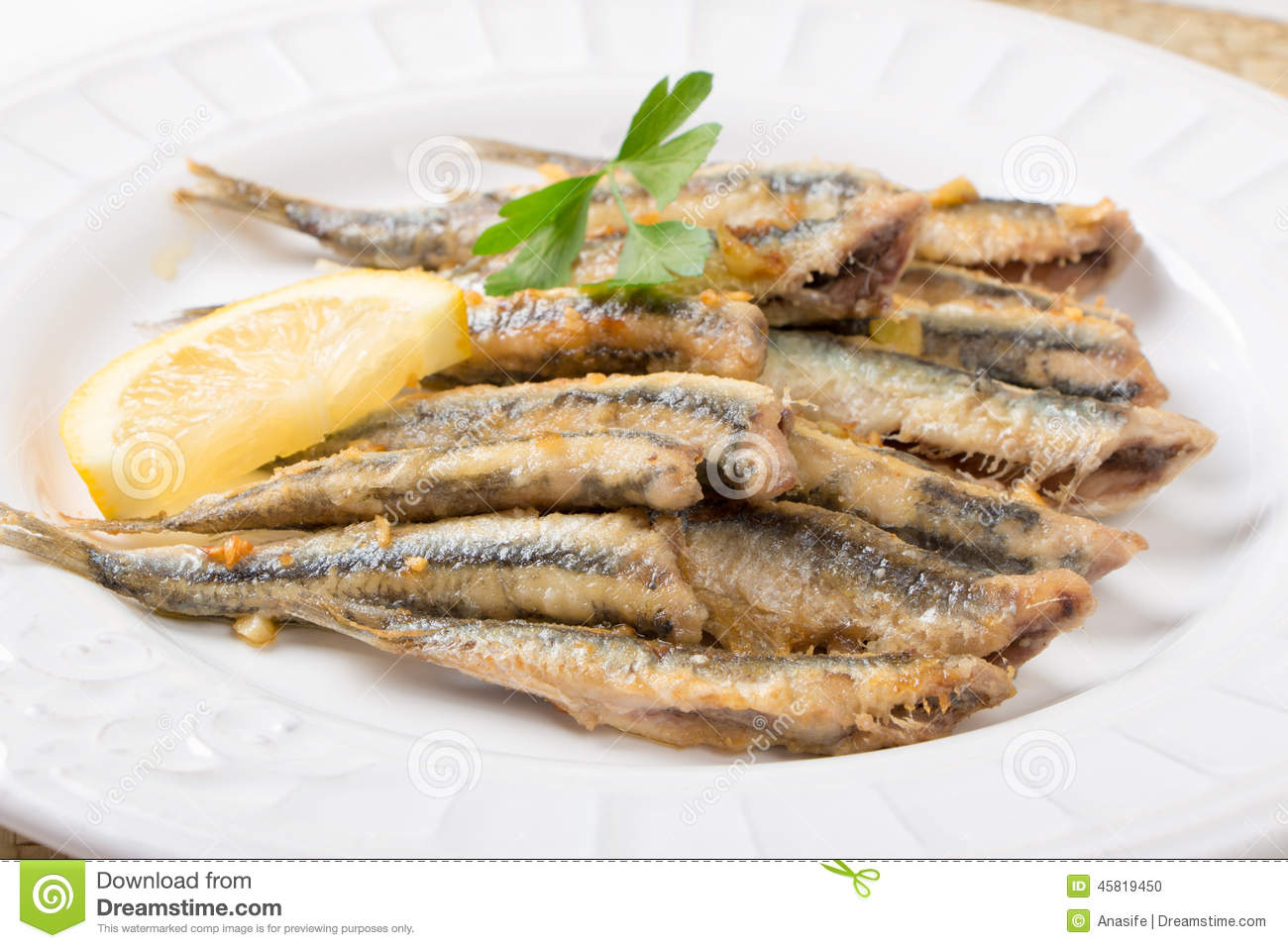 Fried anchovies with parsley and lemon in a dish.