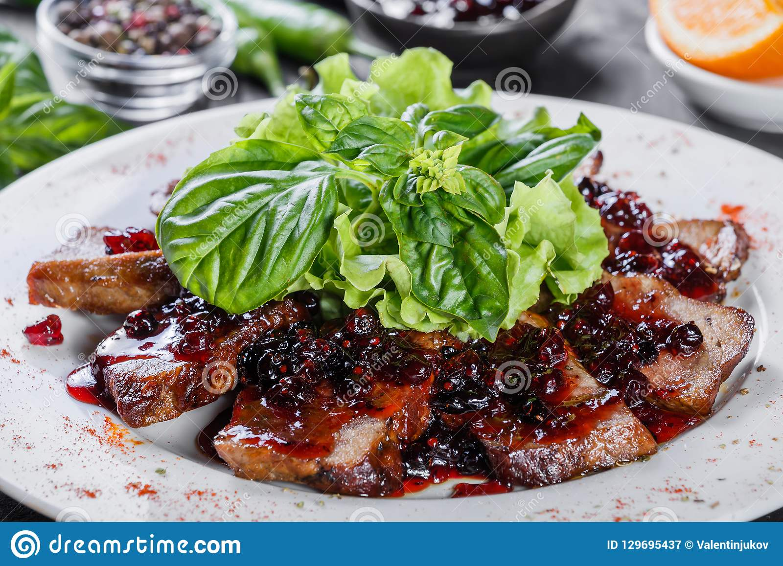 Fried beef meat with wild berries sauce on plate on wooden background.