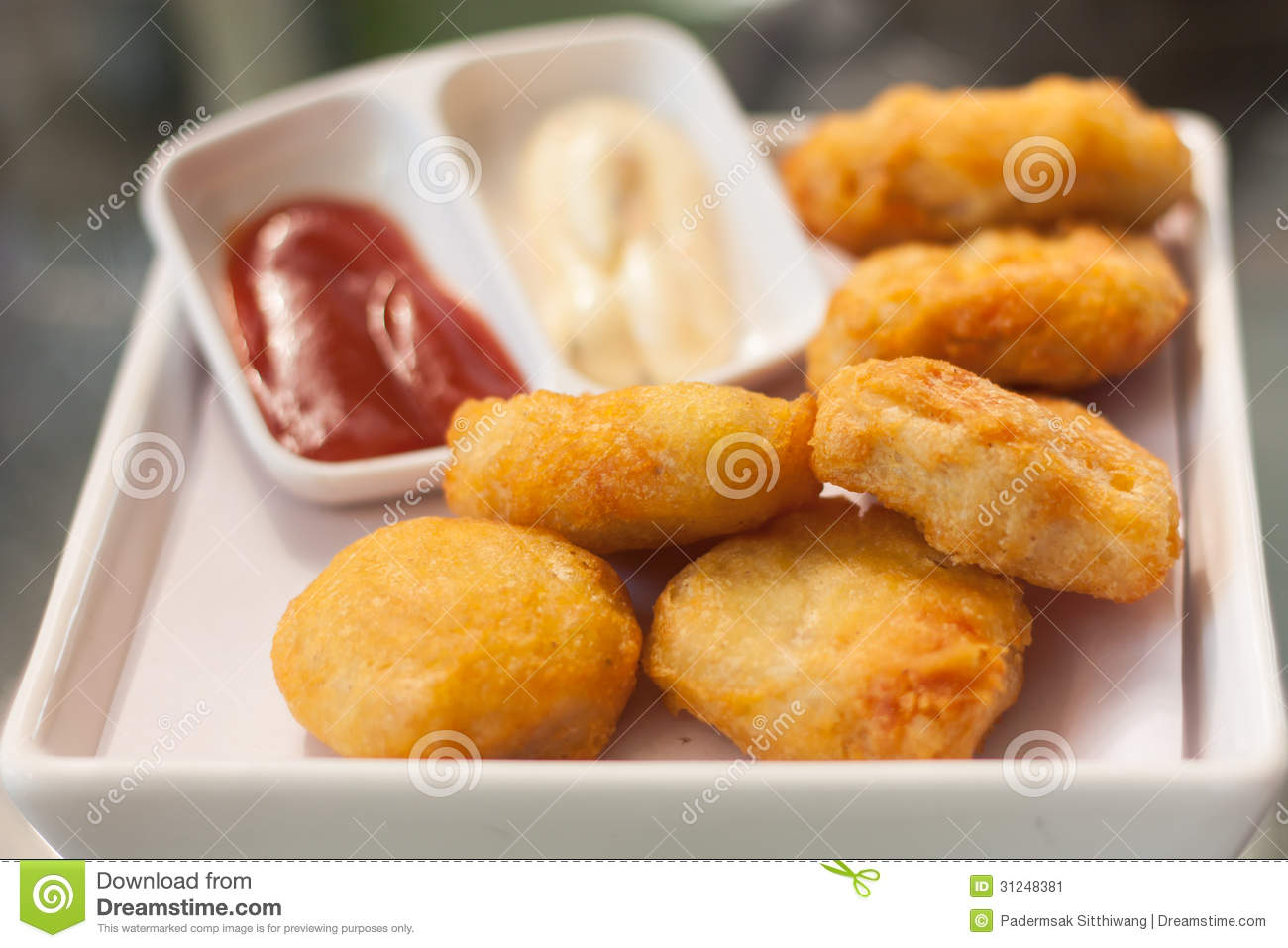 Crispy Fried Chicken nuggets in white plate with sauce.