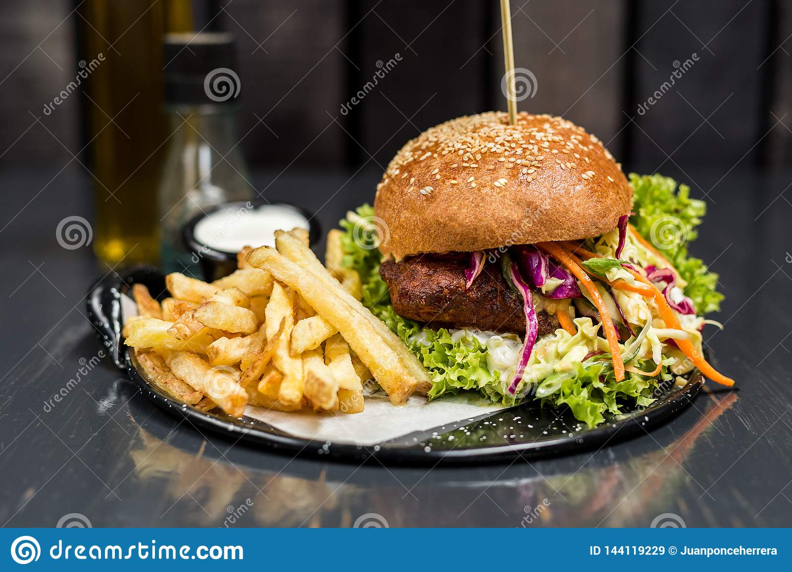 Fried chicken sandwich with vegetables and french fries on a wooden table