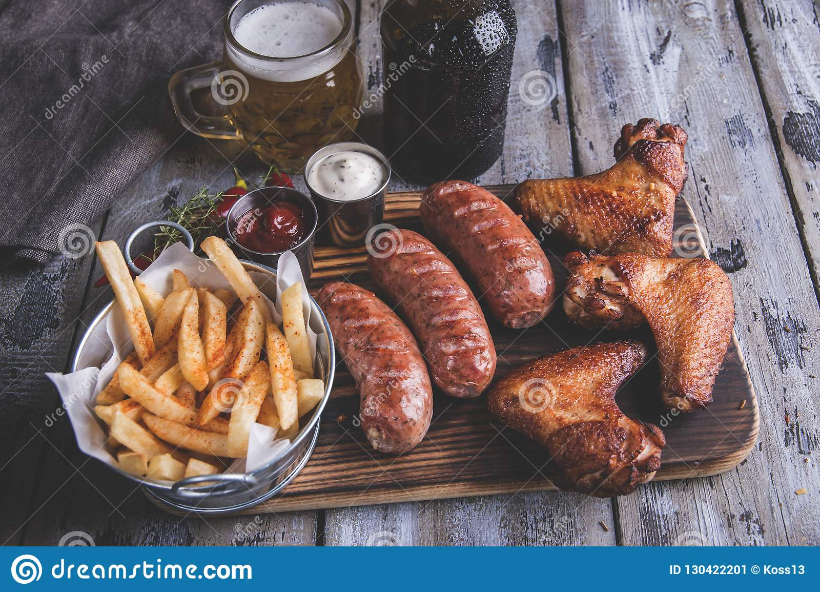 Fried chicken wings,grilled sausages, french fries, nuts, white and red sauce. food to beer